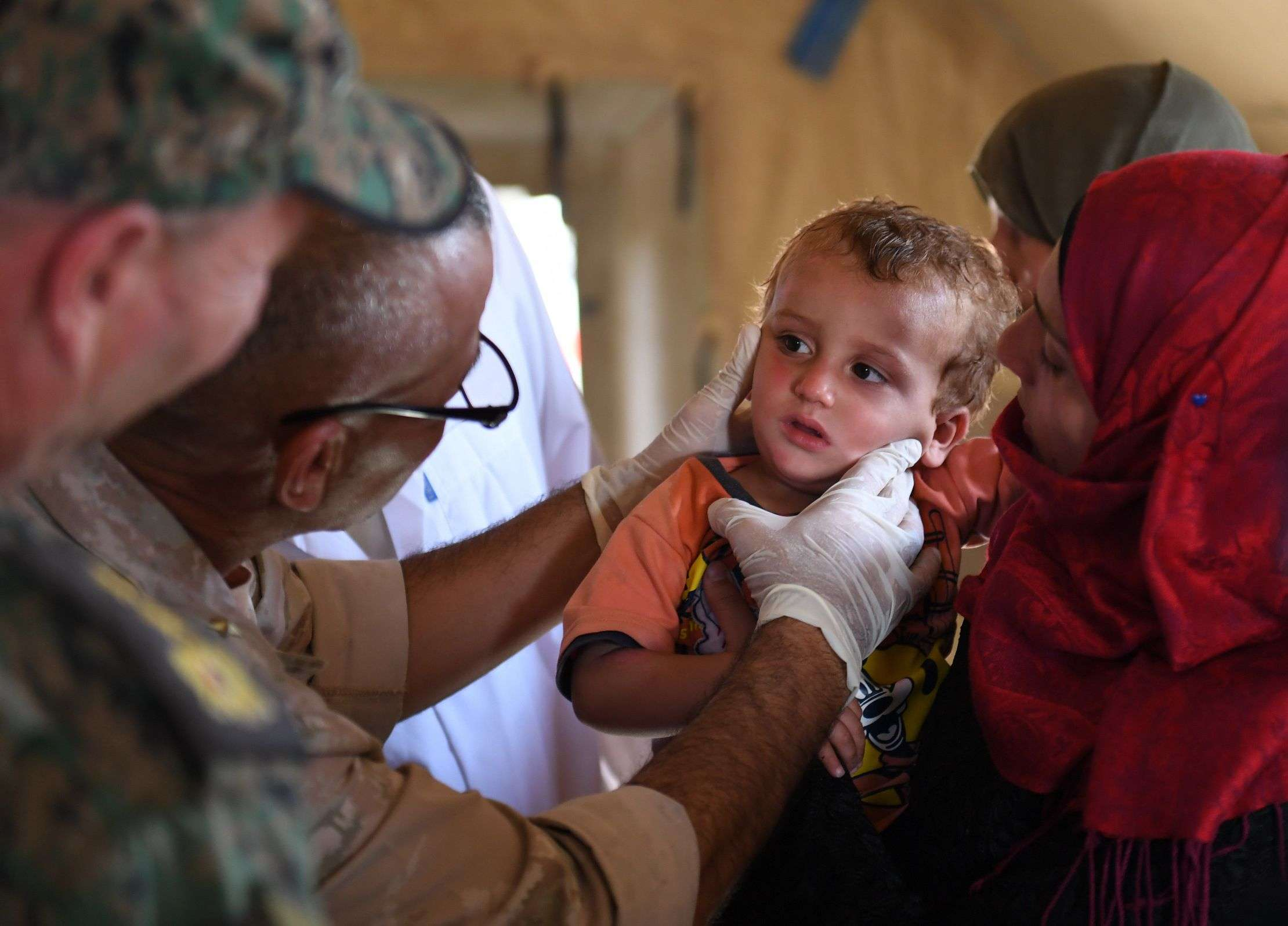 Charm offensive. A Russian soldier gives medical aid to Syrians at the Abu Duhur crossing on the eastern edge of Idlib province, on September 25. (AFP)