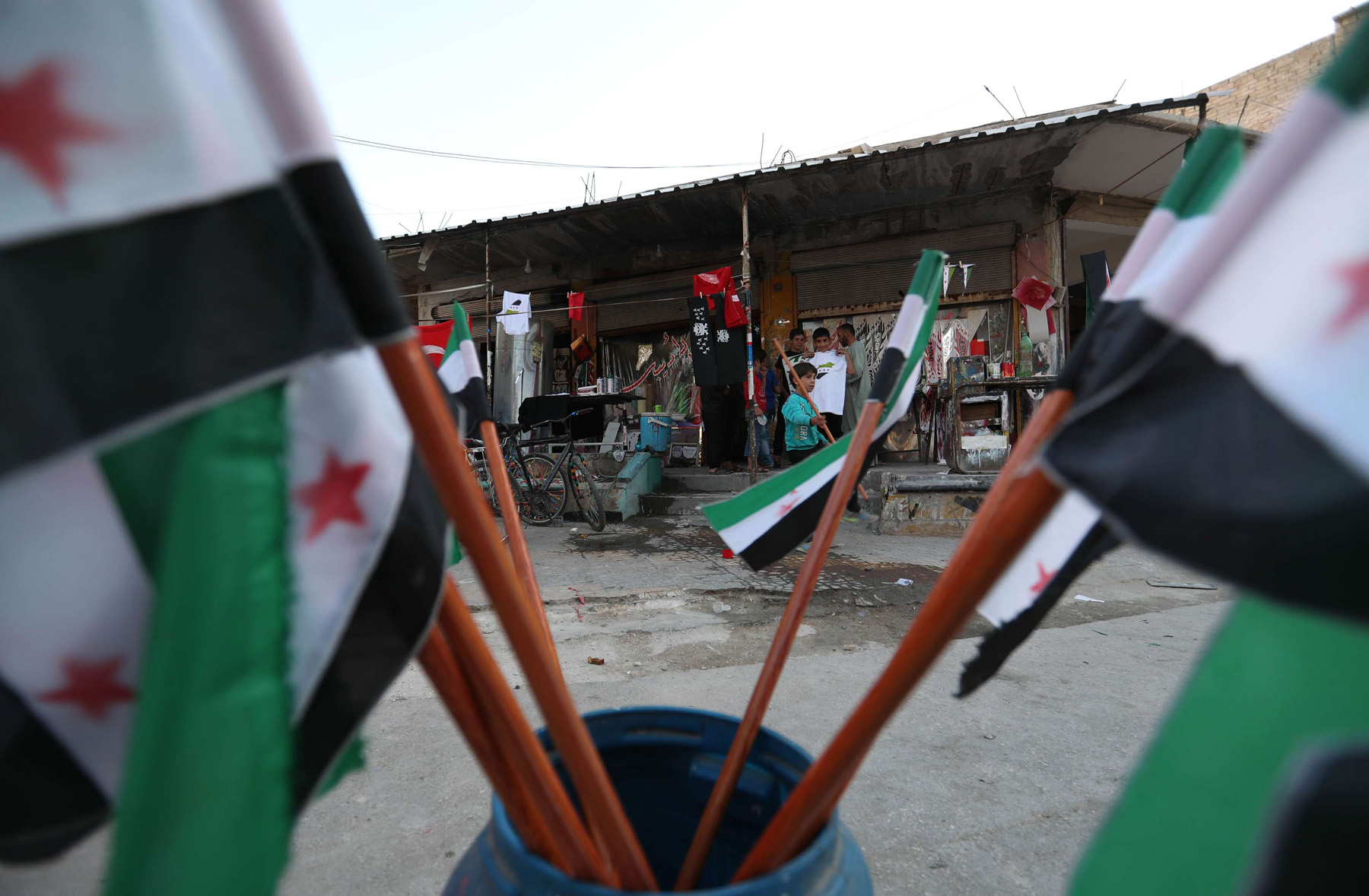 Freshly dyed Syrian opposition flags are seen hanging out to dry outside shops in the rebel-held town of Maaret al-Numan, in the north of Idlib province on September 27, 2018. (AFP)