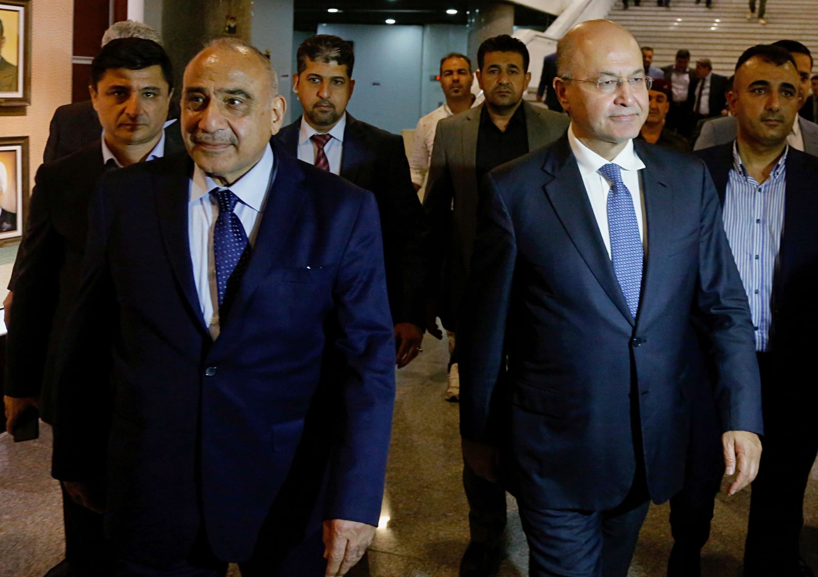 Iraq's new President Barham Salih, center right, walks with new Prime Minister Adel Abdul-Mahdi, center left, in the parliament building in Baghdad, Iraq, Tuesday, October 2, 2018. (AP)