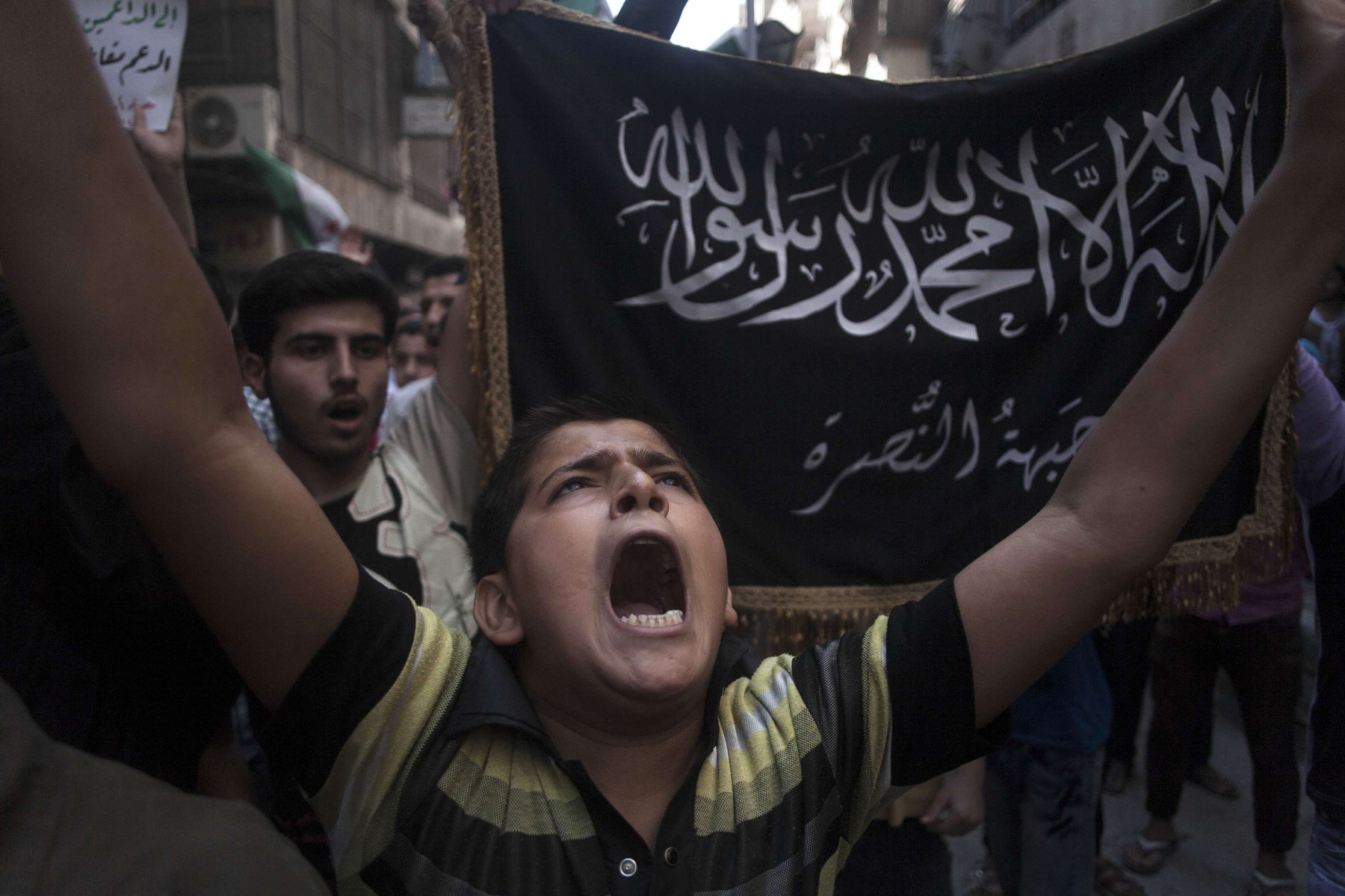 A Syrian boy shouts slogans against the Syrian government in front of a flag of the armed Islamic opposition group, the Nusra front, during a demonstration in Aleppo, Syria. (AP)