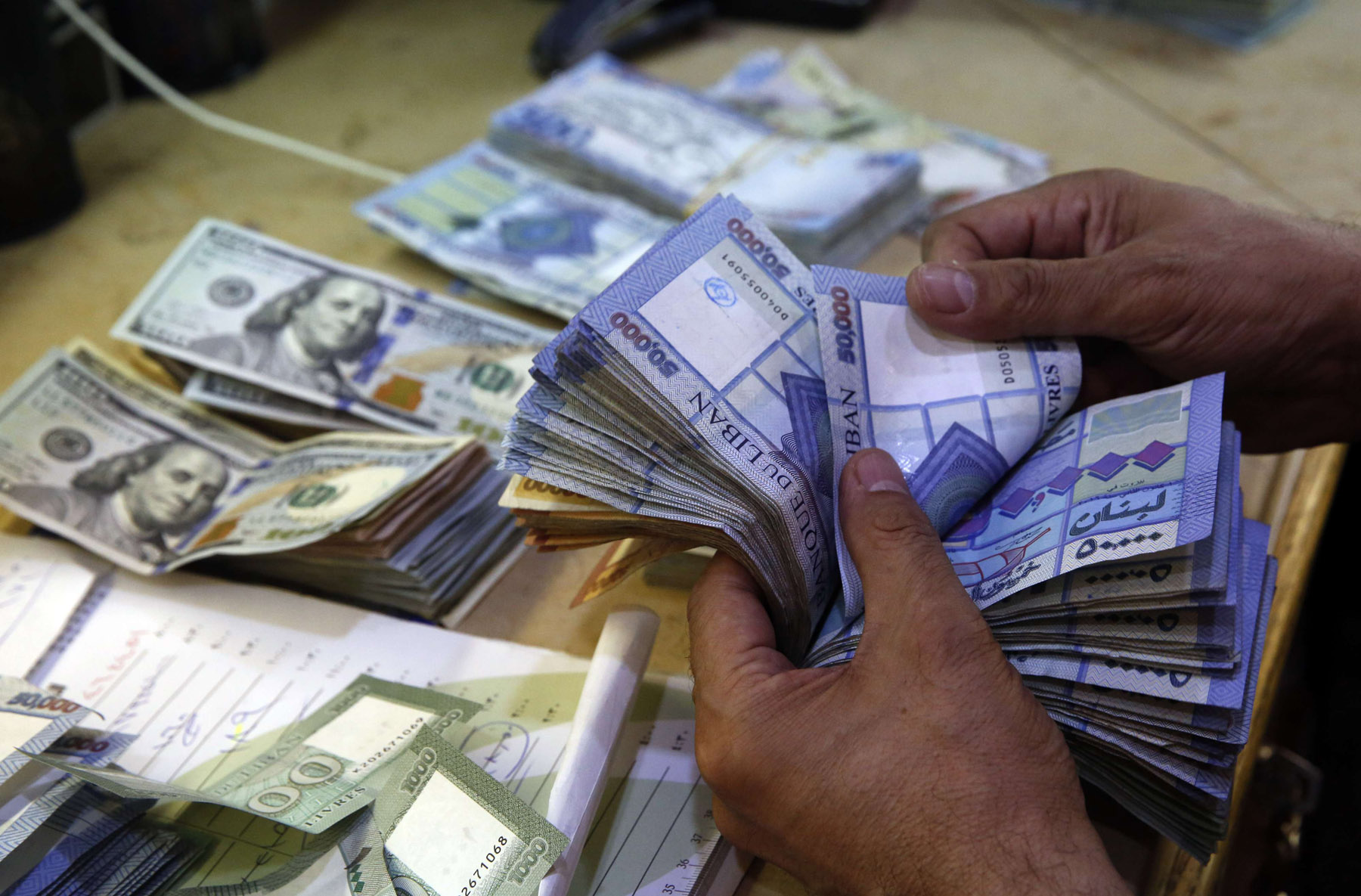 A man counts Lebanese pound notes at an exchange shop in Beirut. (AP)