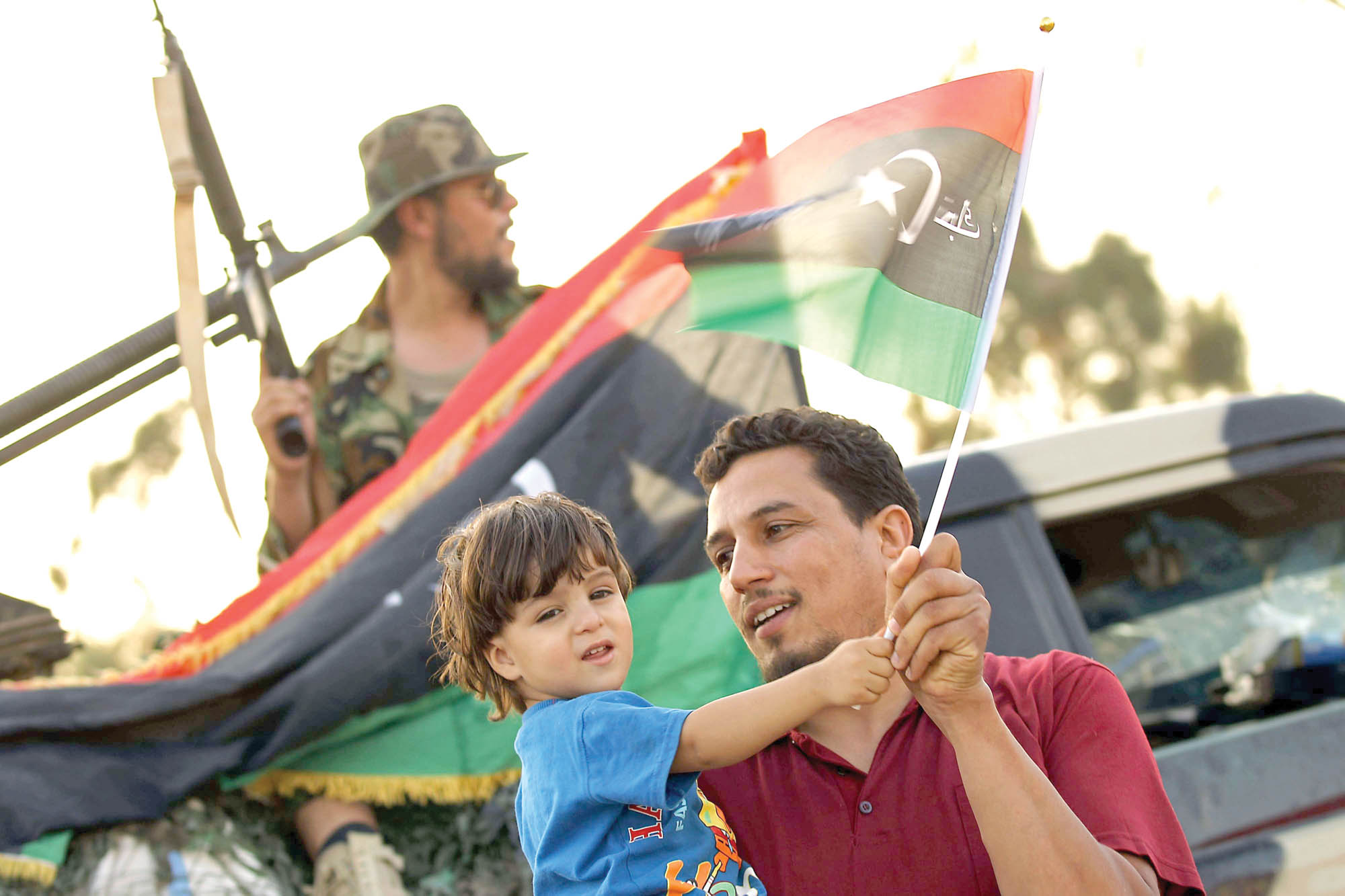 A Libyan man holds a boy waving their national flag in the eastern city of Benghazi. (AFP)