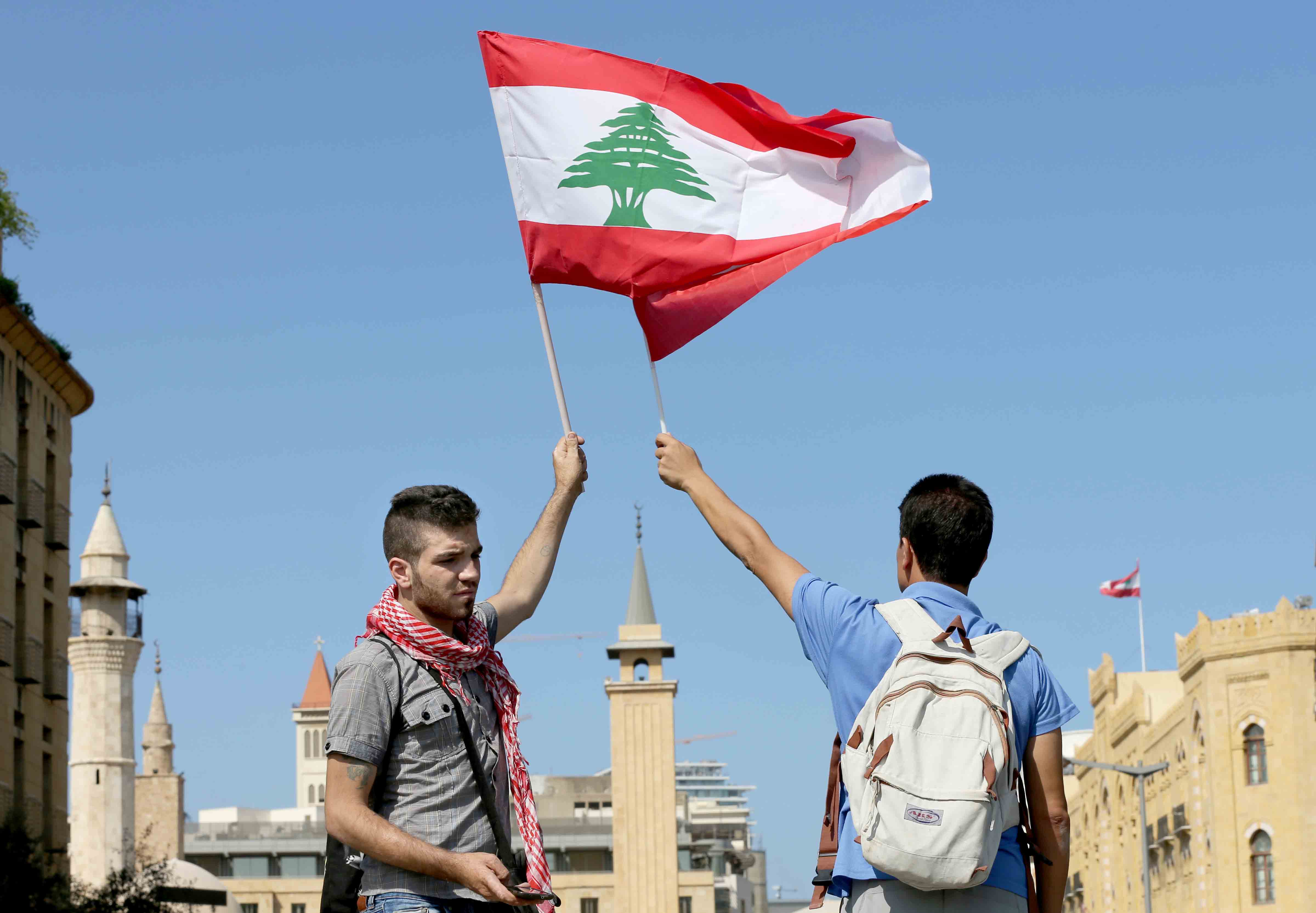 Young men wave Lebanese flags as they gather on a road leading to the parliament building in Beirut. (AP)