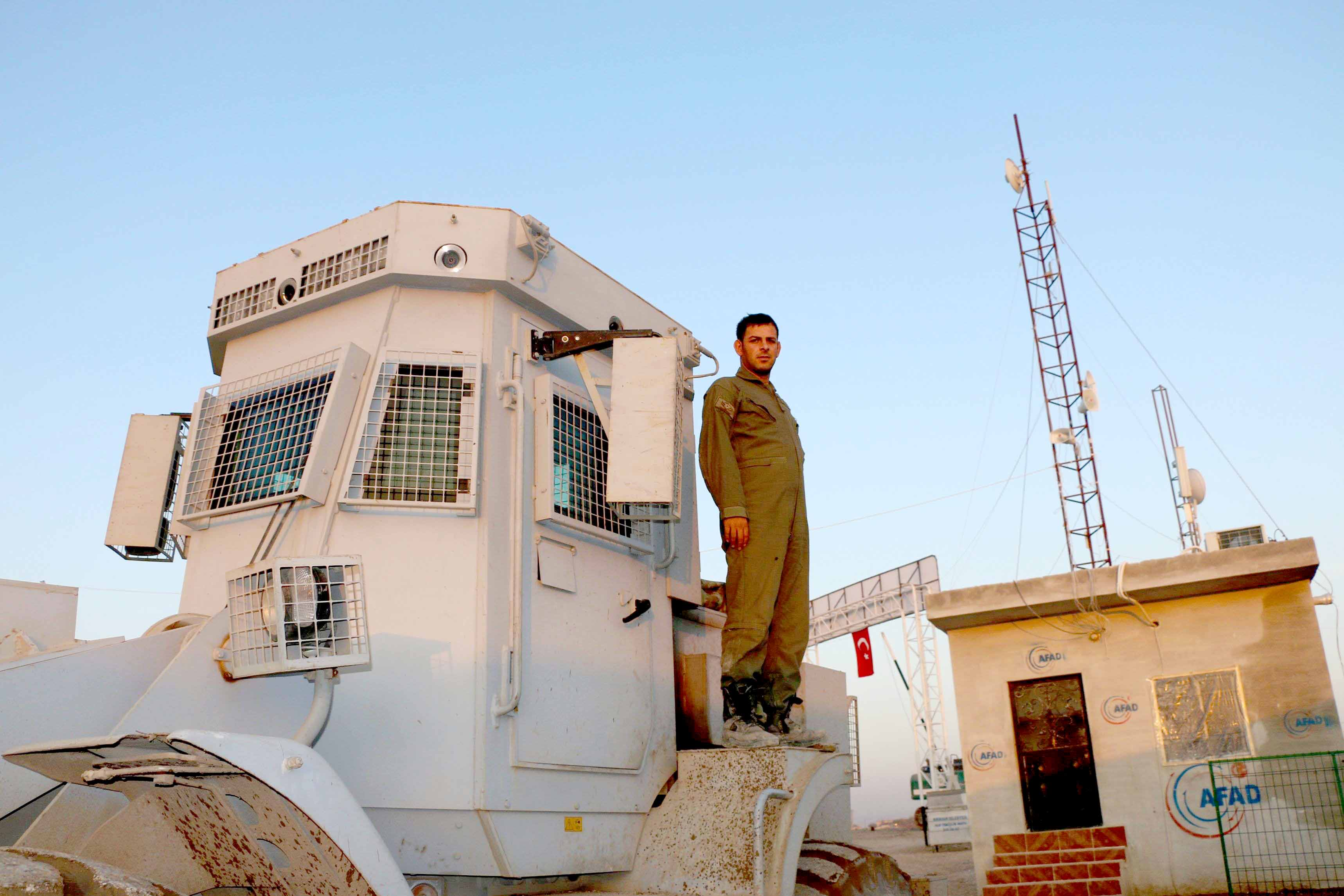 Falling apart. A Turkish soldier stands atop a bulldozer at a camp for the Syrian displaced in the Deir al-Ballut refugee camp in Afrin's countryside, on November 19. (AFP)