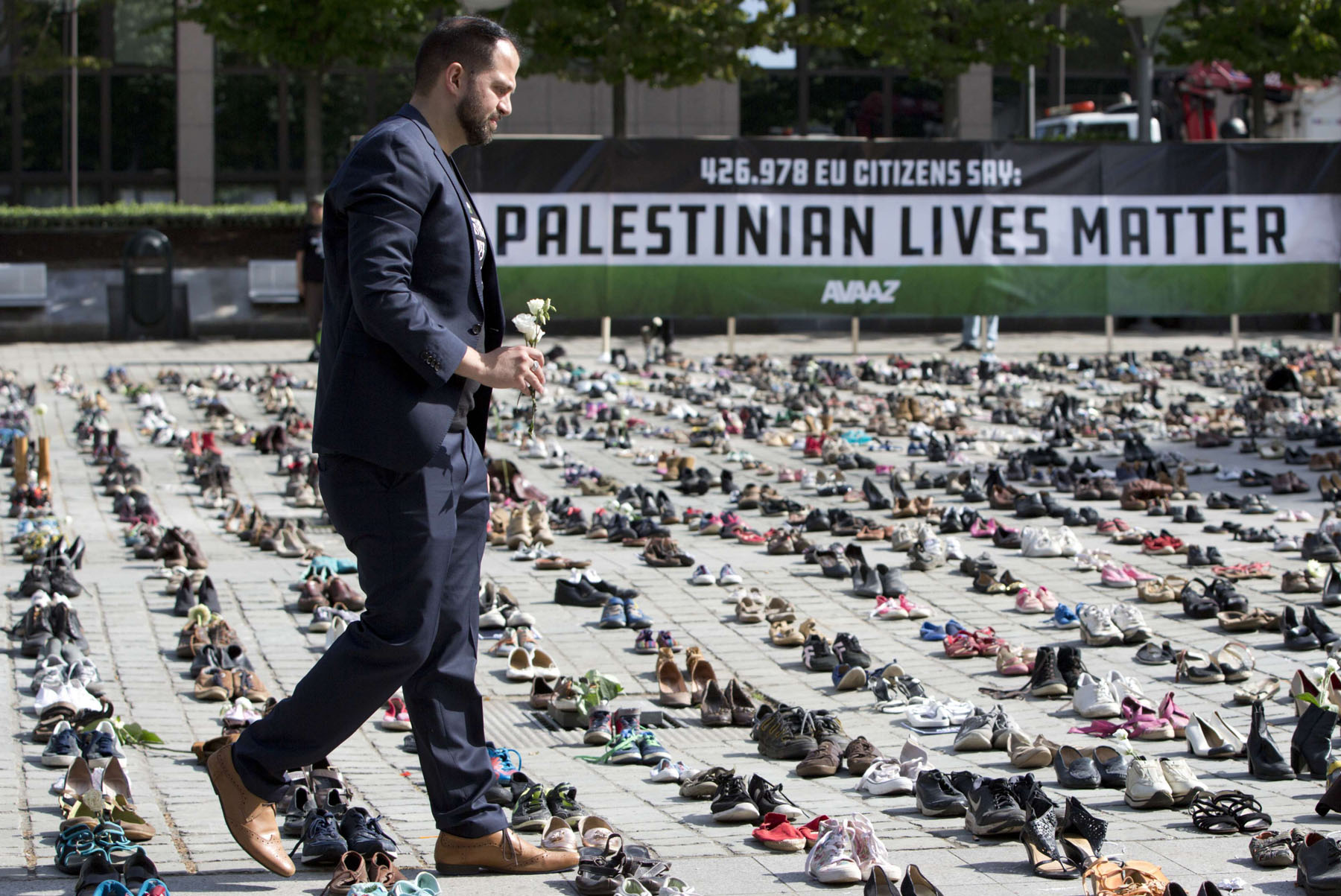 A man walks with flowers in Brussels among pairs of shoes during a demonstration in solidarity with Palestinians. (AP)
