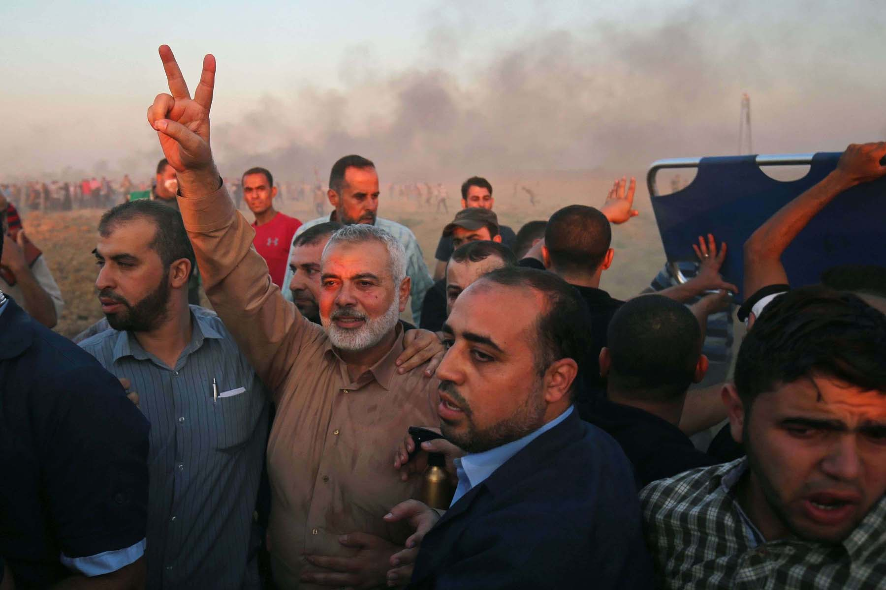 Hamas leader Ismail Haniya (C) flashes the victory sign at the Israel-Gaza border, on October 12. (AFP)