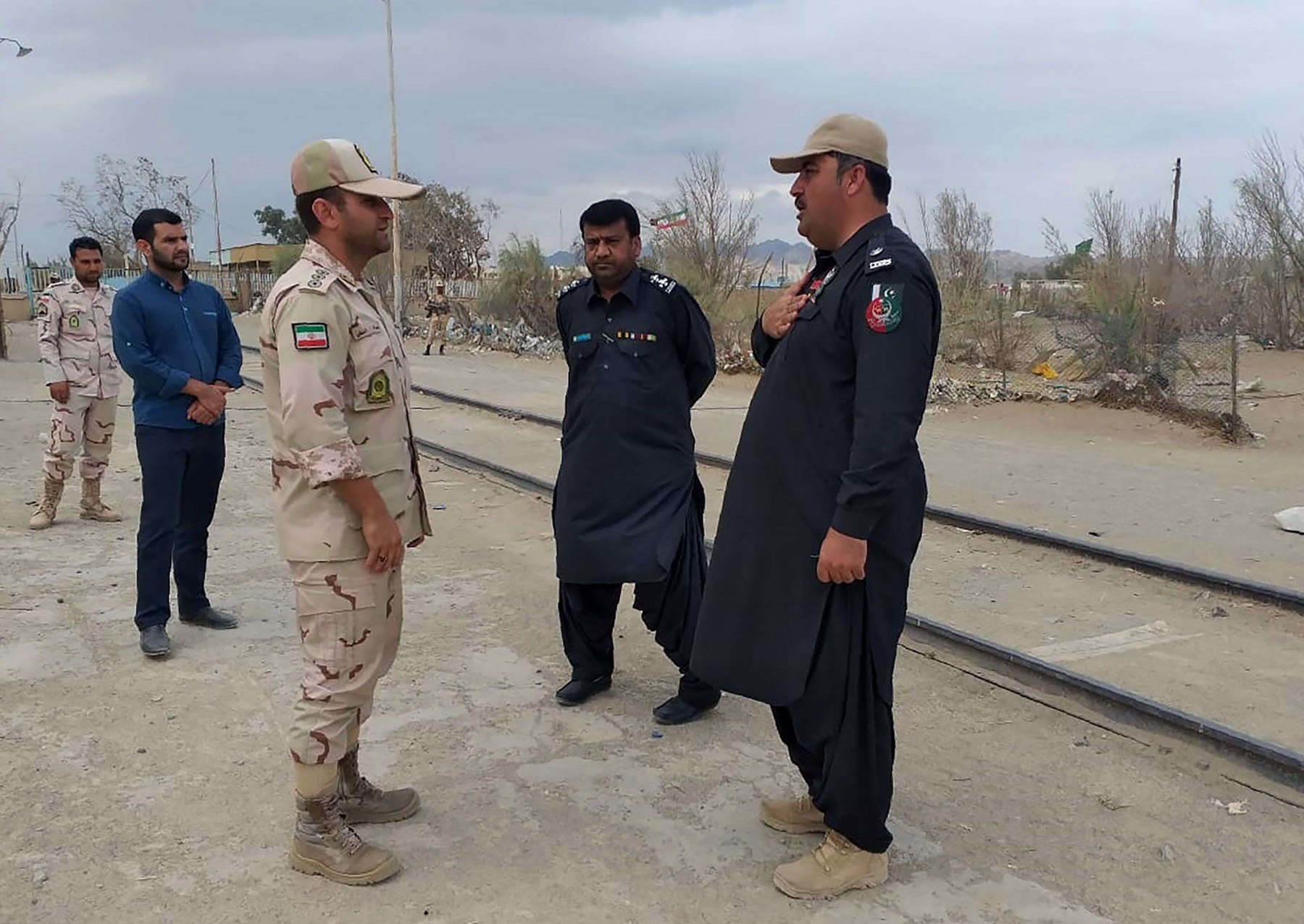 A Pakistani border security official (R) and an Iranian border official meet at Zero Point in the Pakistan-Iran border town of Taftan, on October 16. (AFP)