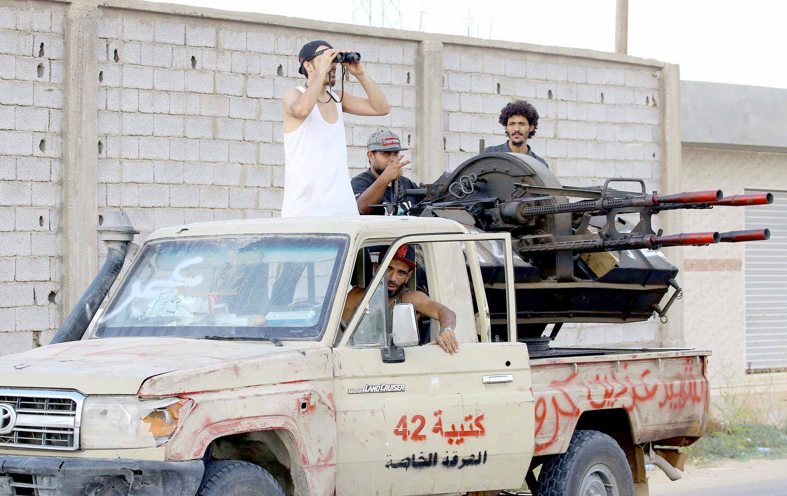A battle for influence. Libyan militiamen loyal to the Government of National Accord (GNA) keep watch from a position south of Tripoli, last September.(AFP)