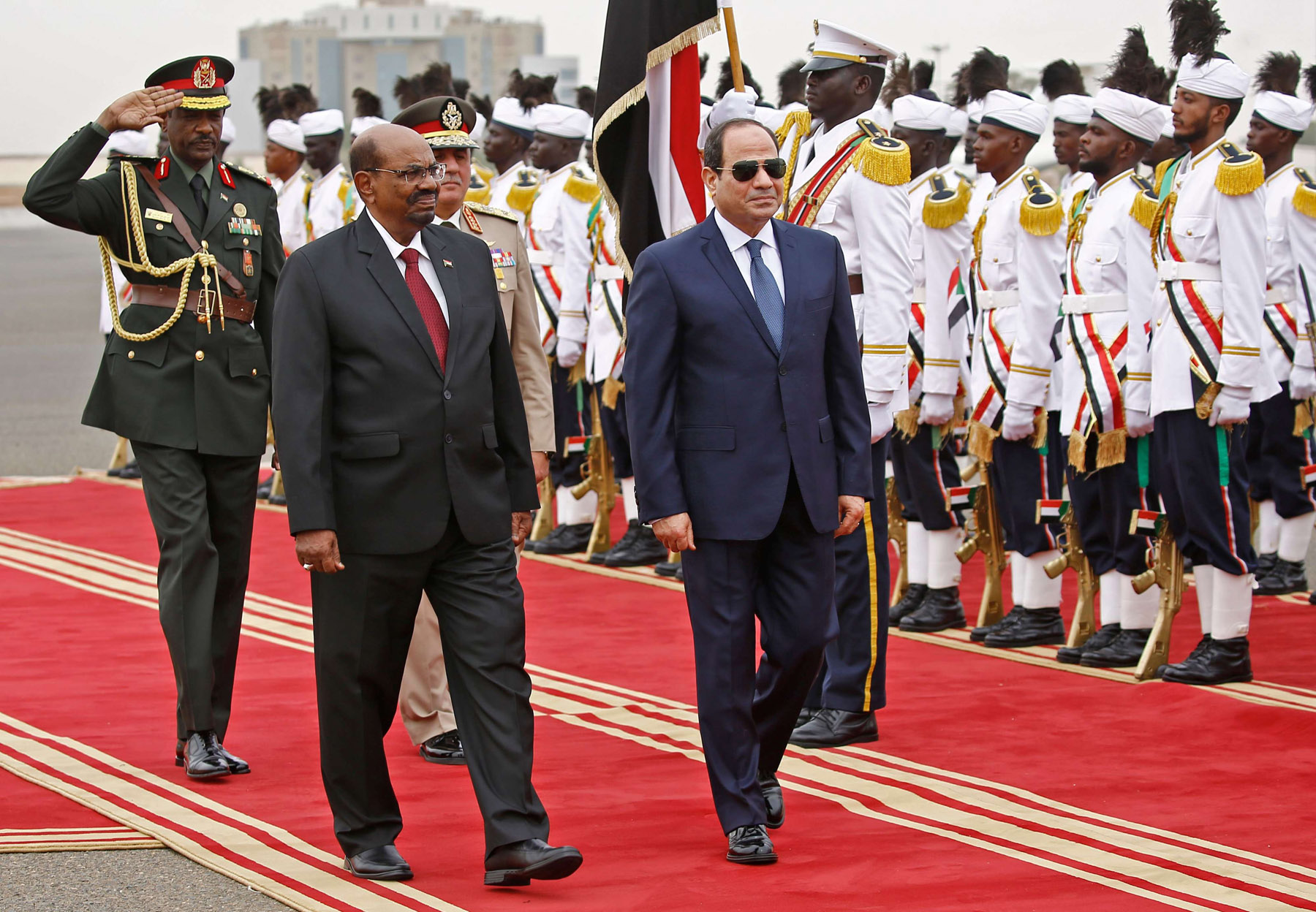 Sudan's President Omar al-Bashir (C-L) inspects an honour guard with his Egyptian counterpart  Abdel Fattah al-Sisi (C-R) in Khartoum, on October 25. (AFP)