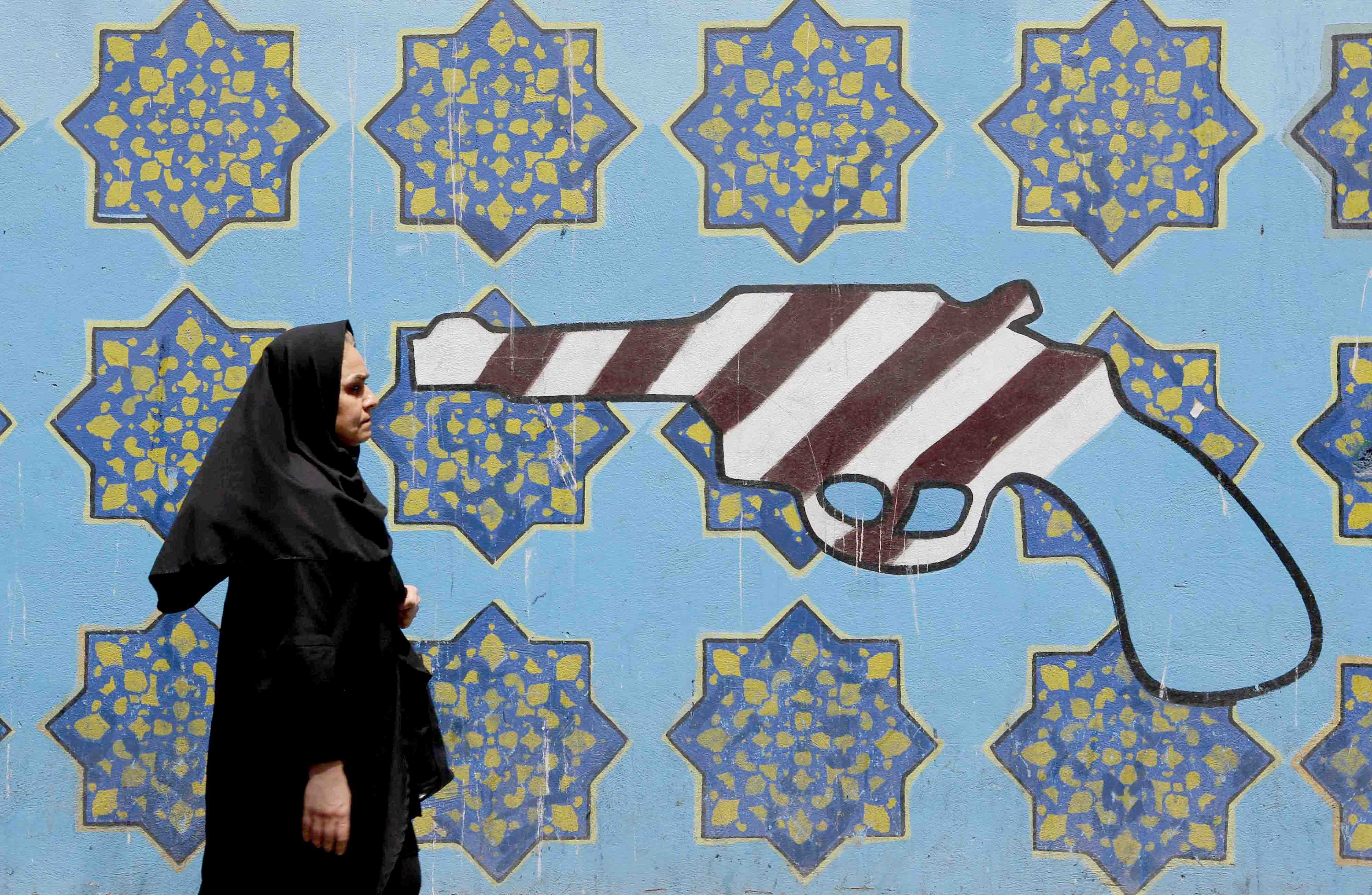An Iranian woman walks by a mural on the wall of the former US embassy in Tehran. (AFP)