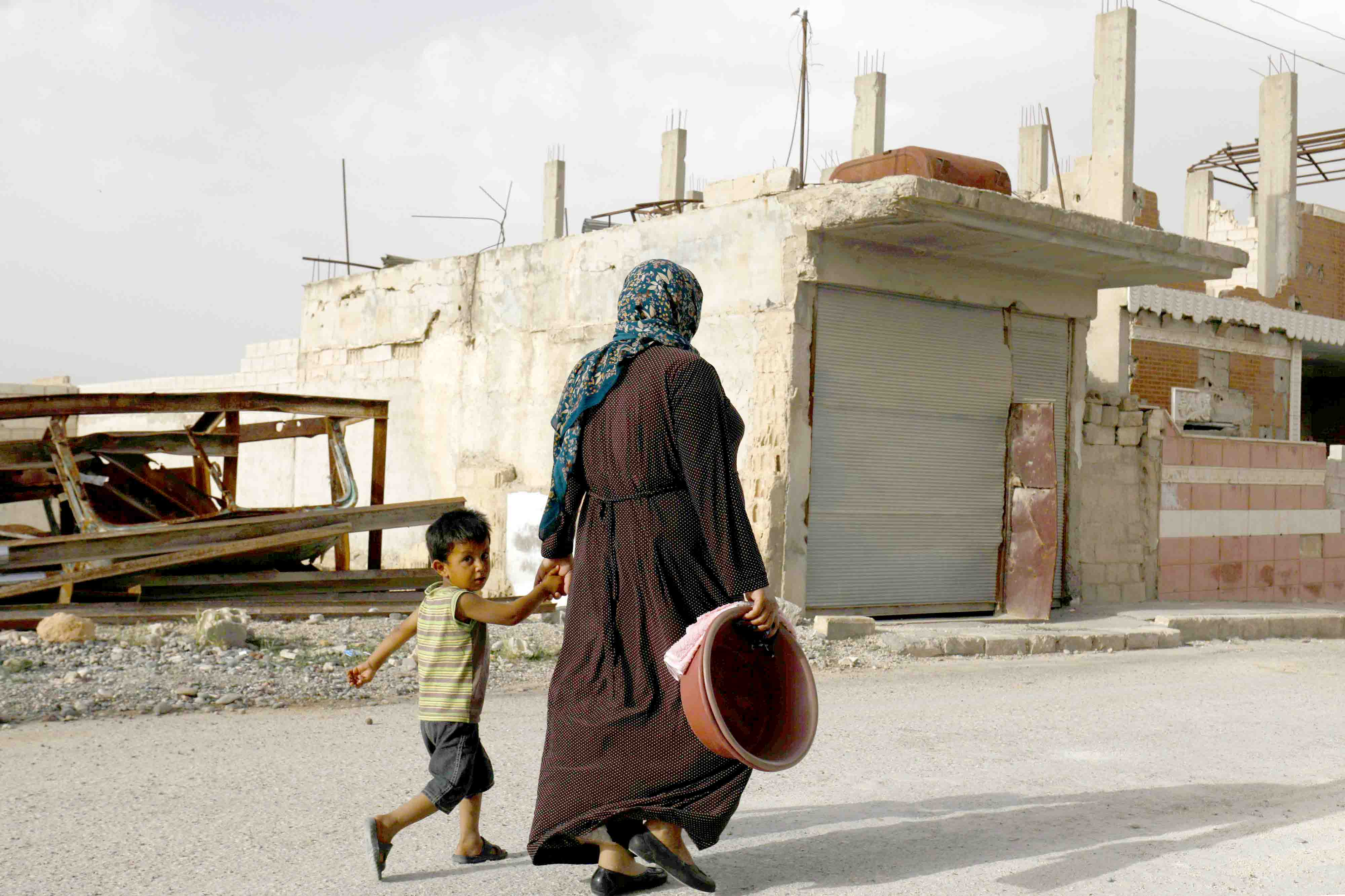 In the line of fire. A Syrian woman walks with her child past destroyed buildings in Kobane. (AFP)