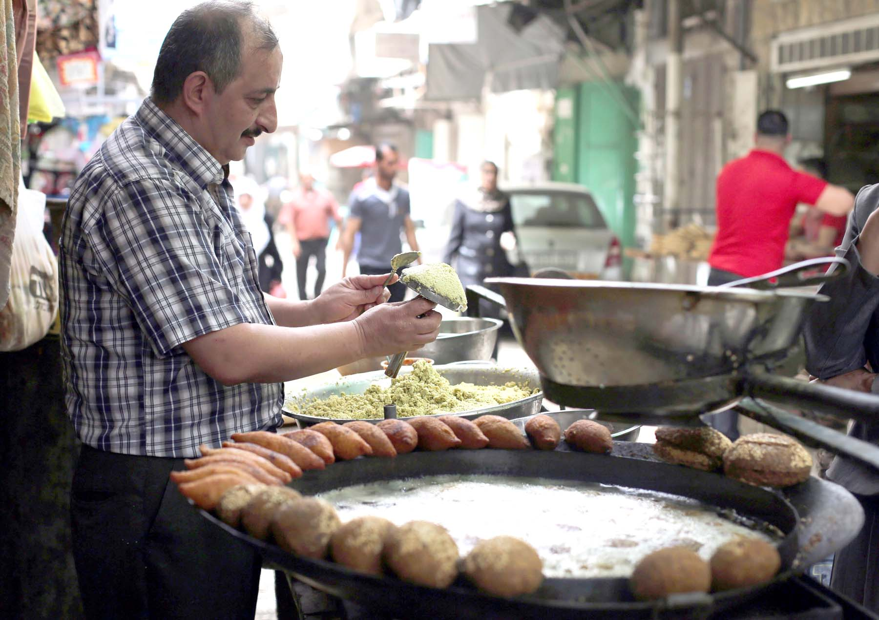 More than what's on a plate. A Palestinian man makes falafel, a  traditional dish consisting of fried chickpeas, on a street in Nablus.   (AFP)
