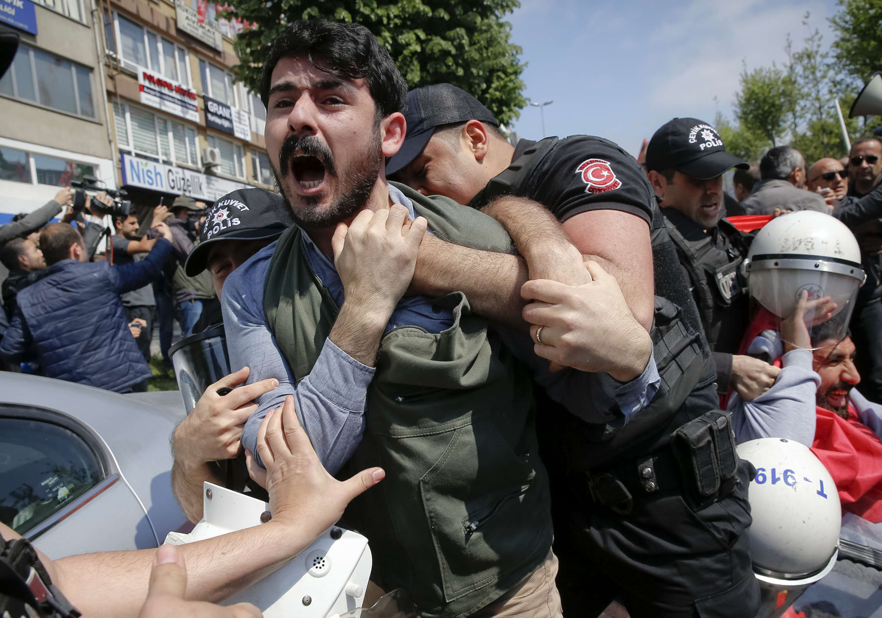 A demonstrator screams as police officers grab him during a protest in Istanbul. (AP)