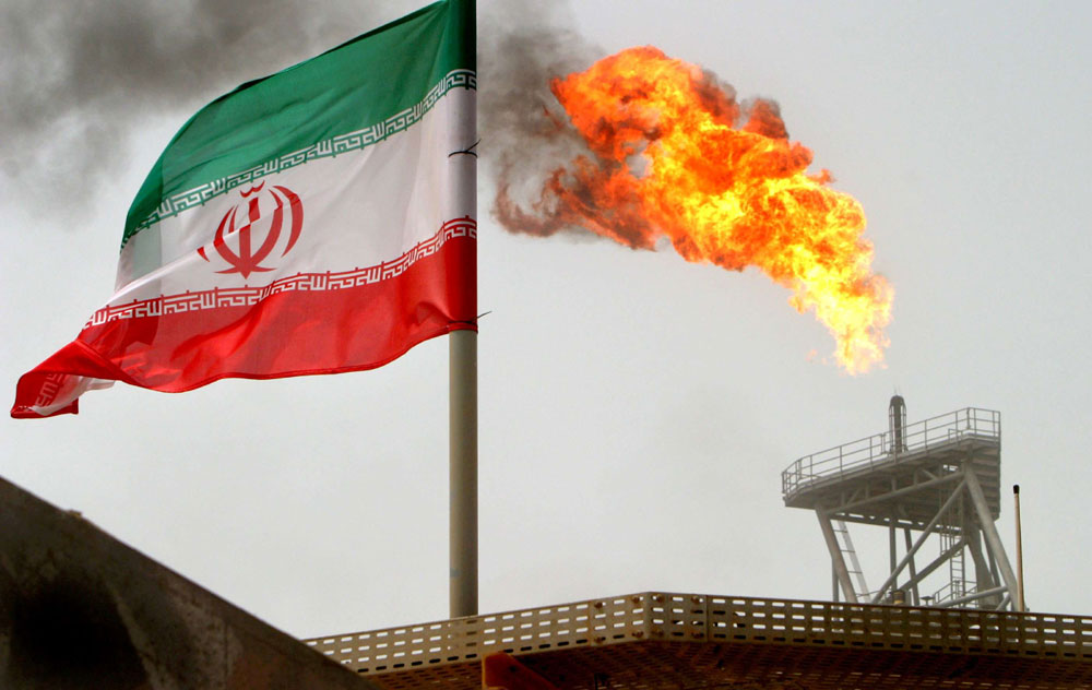 A gas flare on an oil production platform in the Soroush oil fields is seen alongside an Iranian flag in the Gulf, last July. (Reuters)