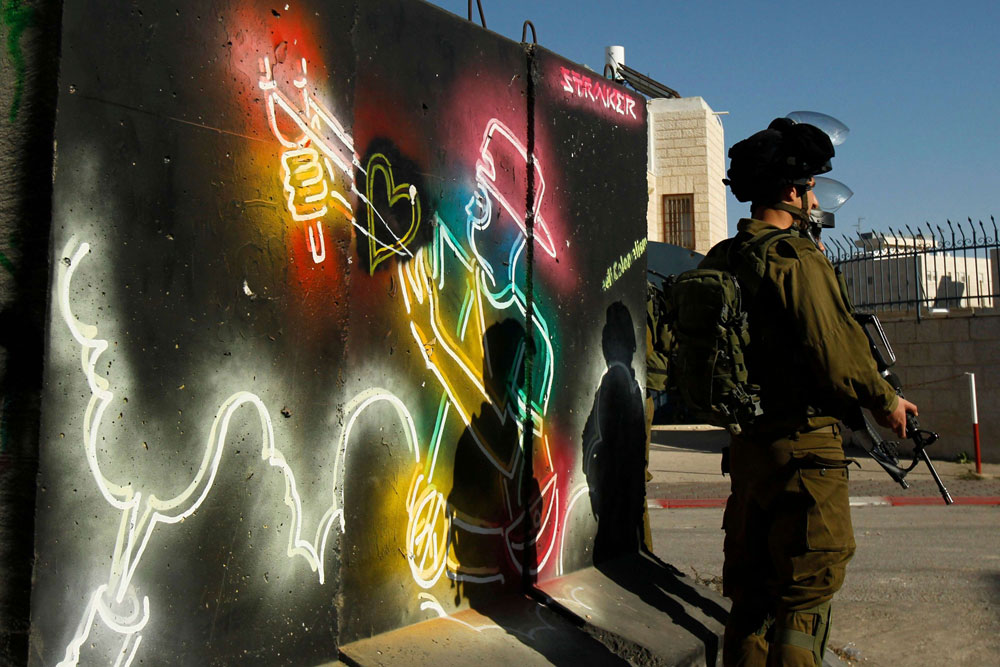 Israeli forces stand guard in front of a mural at the main entrance of the Palestinian city of Bethlehem in the occupied West Bank. (AFP)