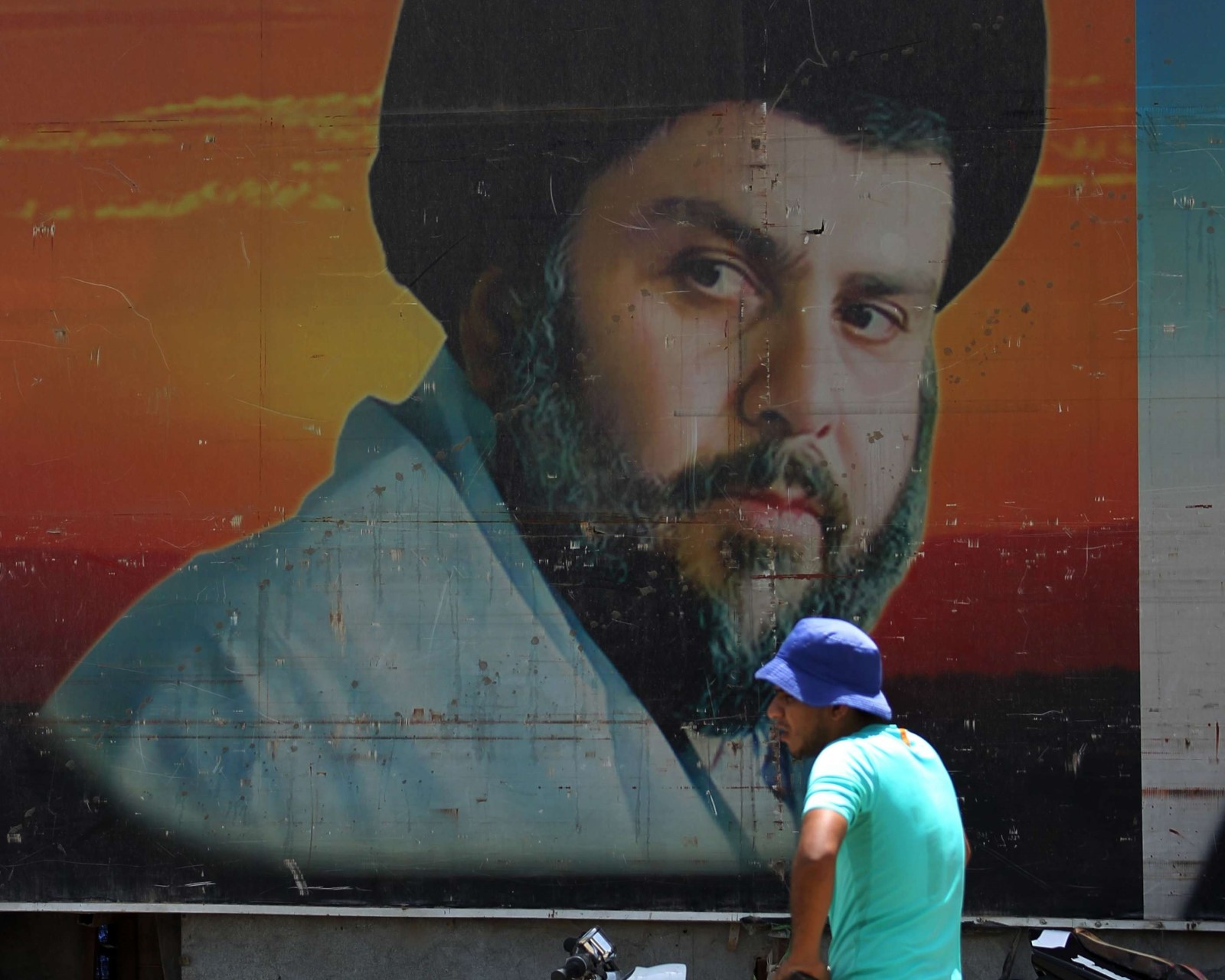 An Iraqi man walks past a poster of Shia cleric Moqtada Sadr in Sadr City, east of Baghdad. (AFP)