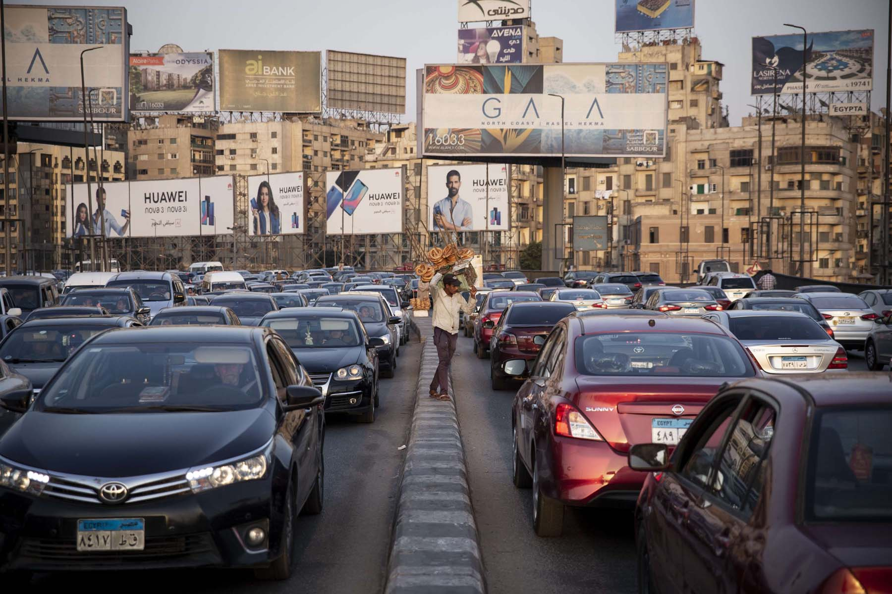 Big market. A street vendor sells snacks to drivers stuck in a traffic jam backdropped by advertising billboards.     (Samer Abdallah)