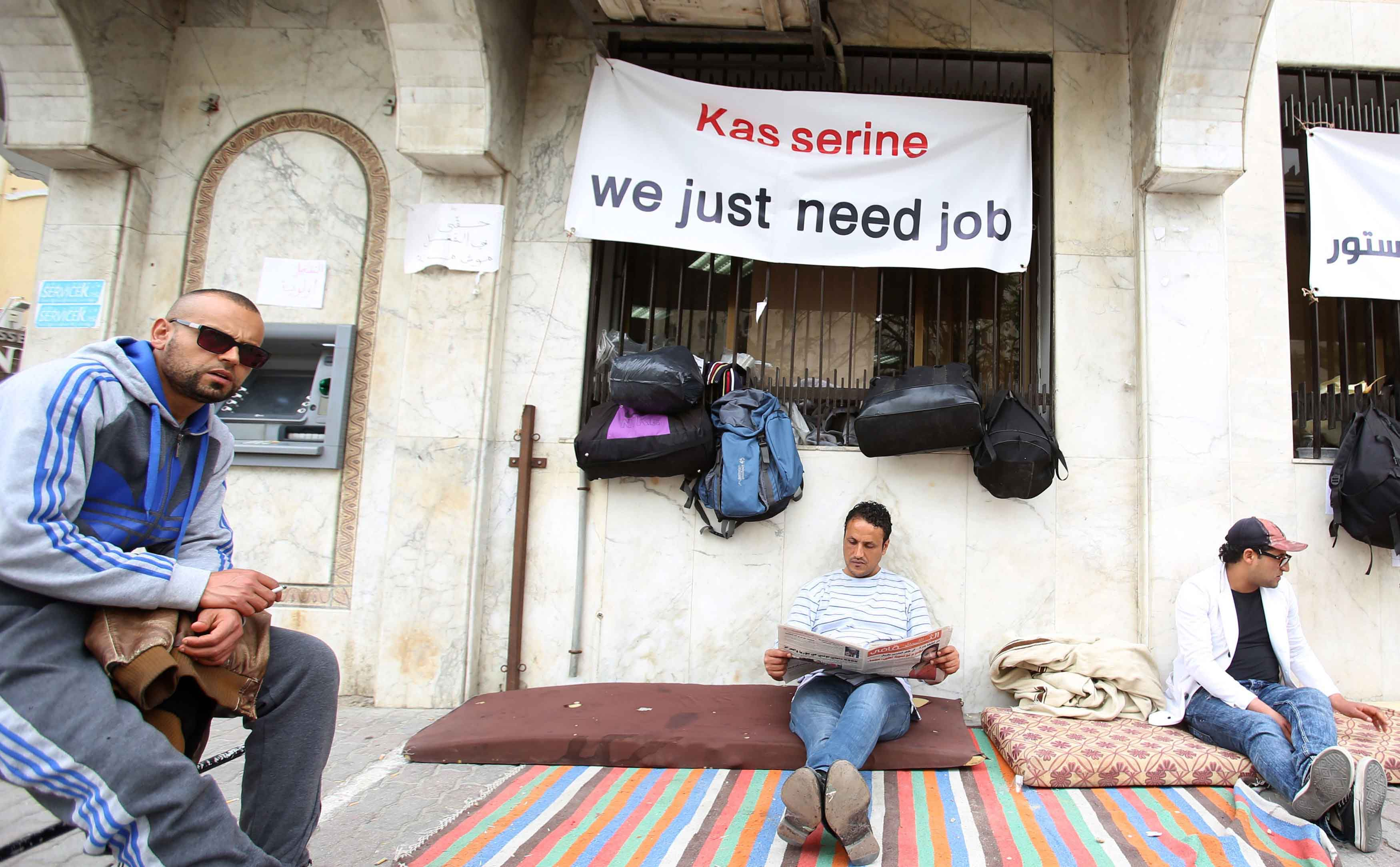 A Tunisian unemployed graduate from the city of Kasserine reads a newspaper as he takes part in a sit-in protest in Tunis. (Reuters)