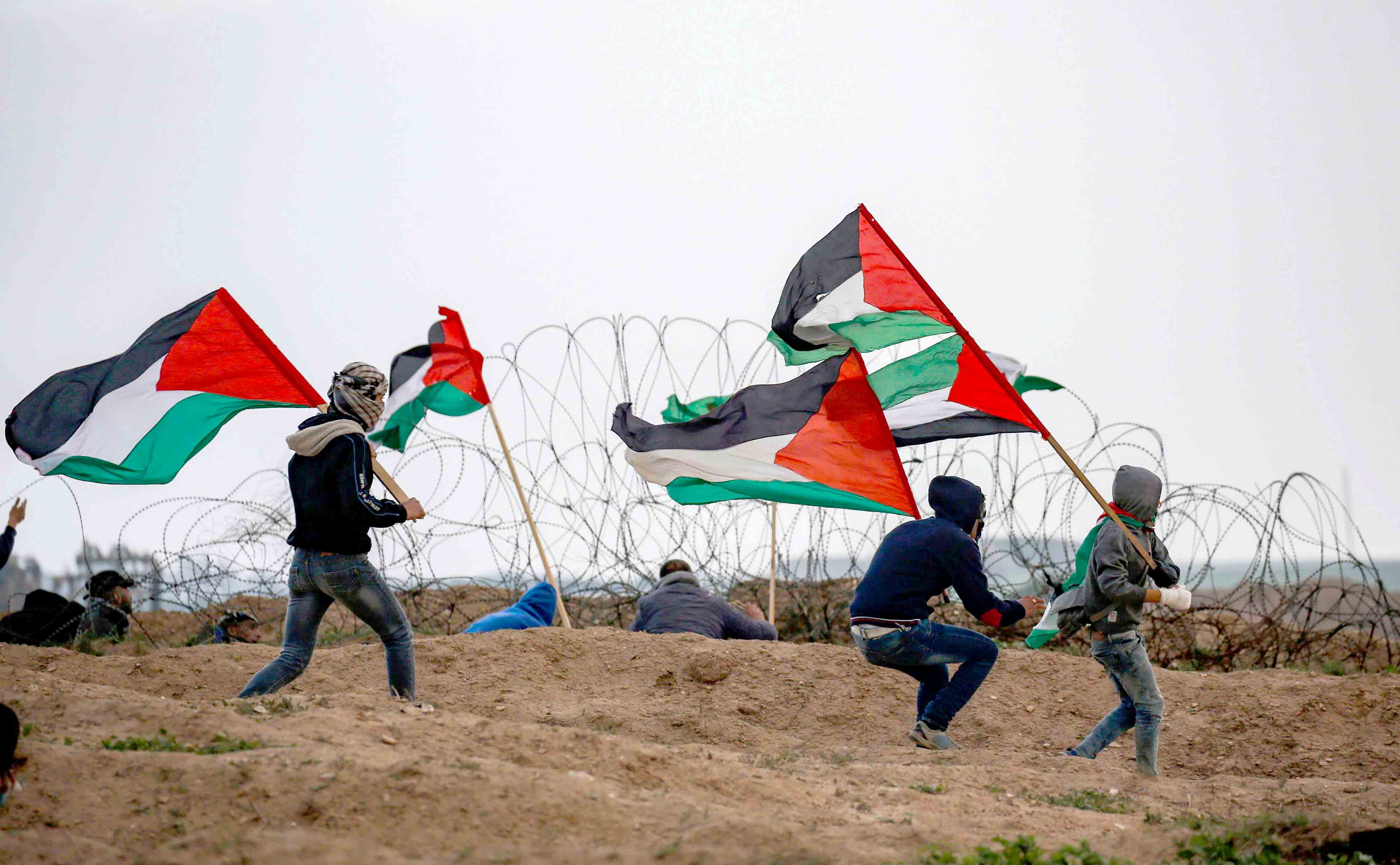 Palestinian youth run carrying Palestinian flags by the barbed wire fence along the border with Israel east of Gaza City, December 7. (AFP)