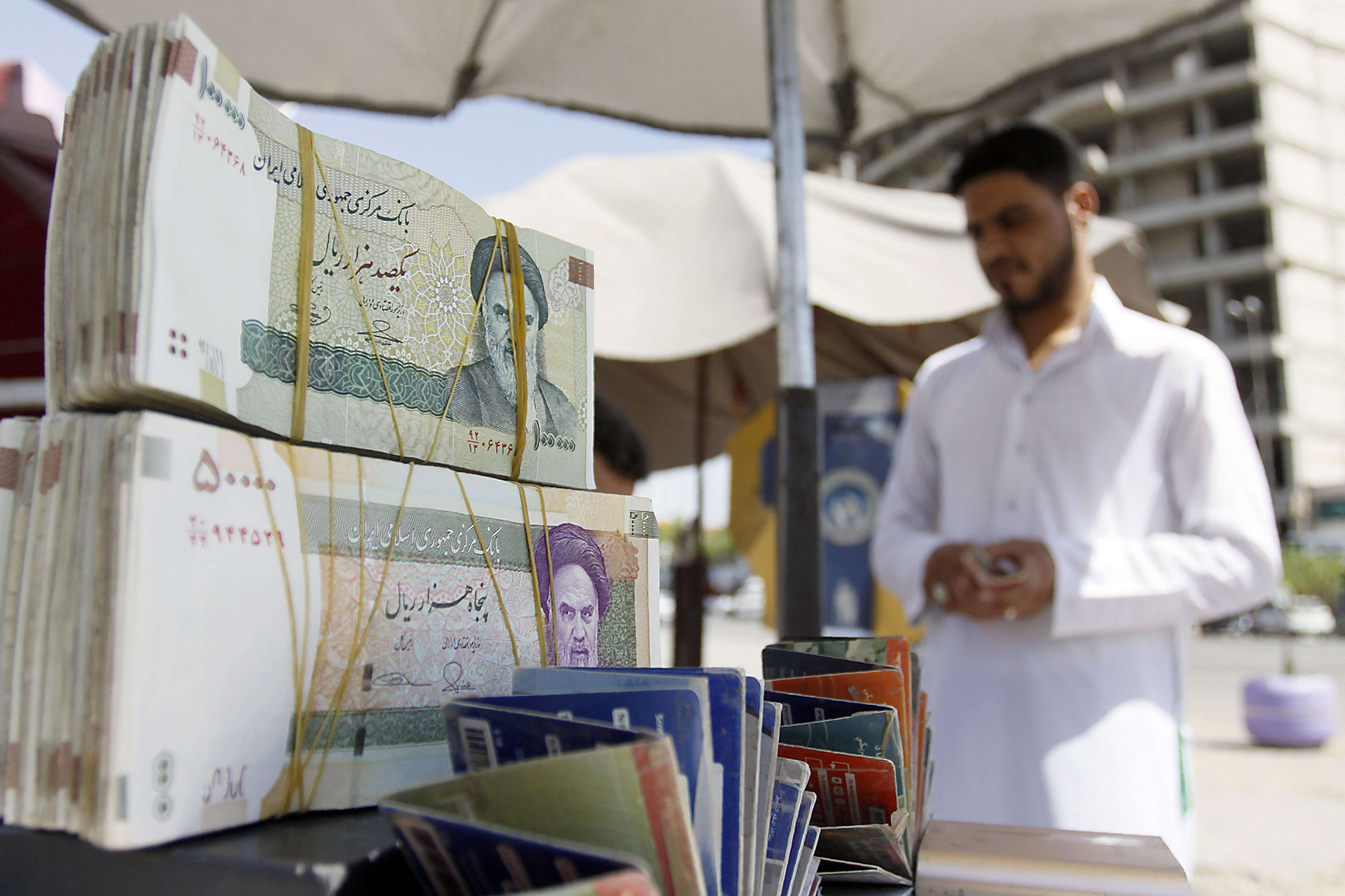 Tug of war. An Iraqi vendor sells Iranian currency in a street in Najaf.  (AFP)
