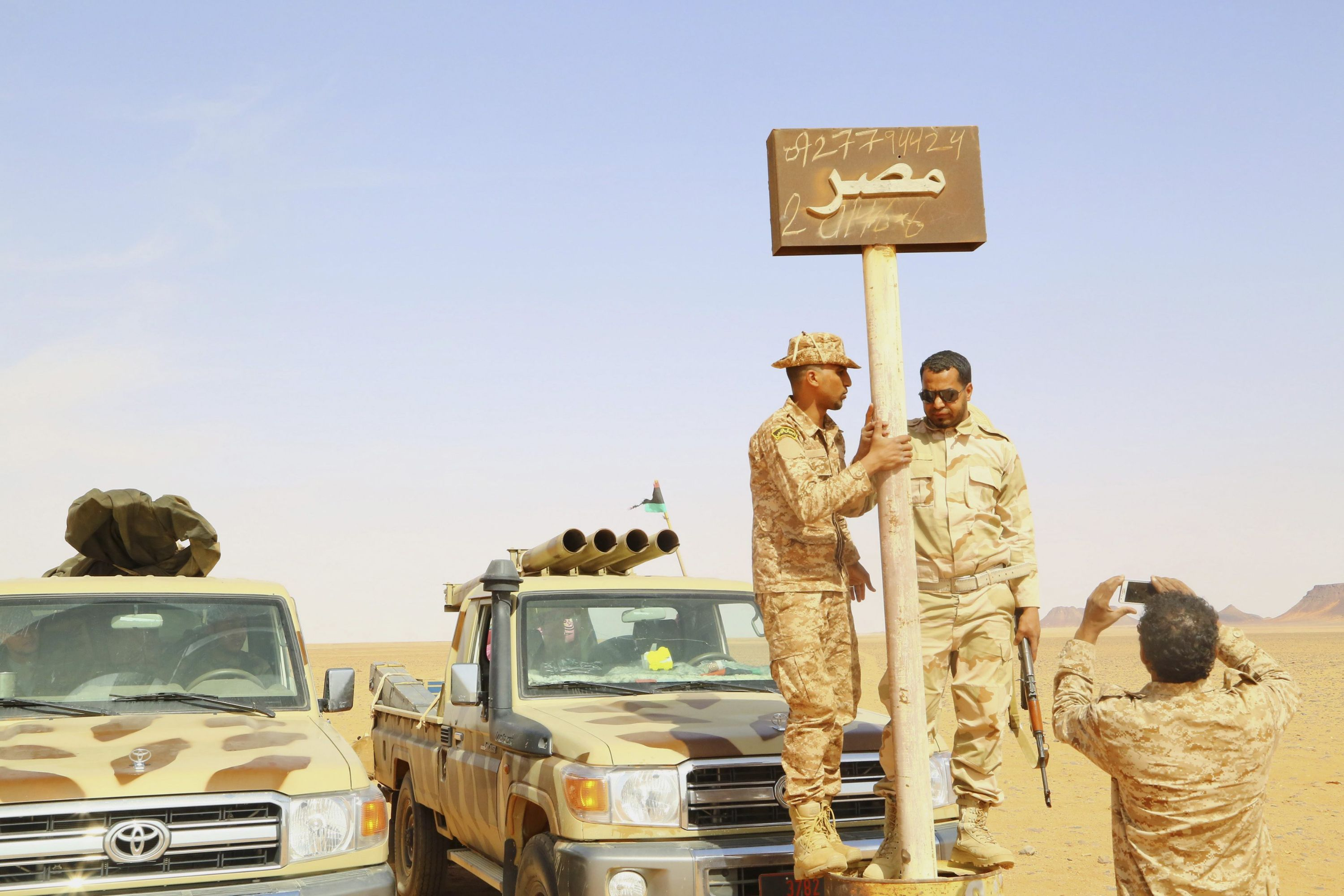 Libyan fighters from Kufra stand next to an Egypt sign at the Libyan-Egyptian border. (Reuters)