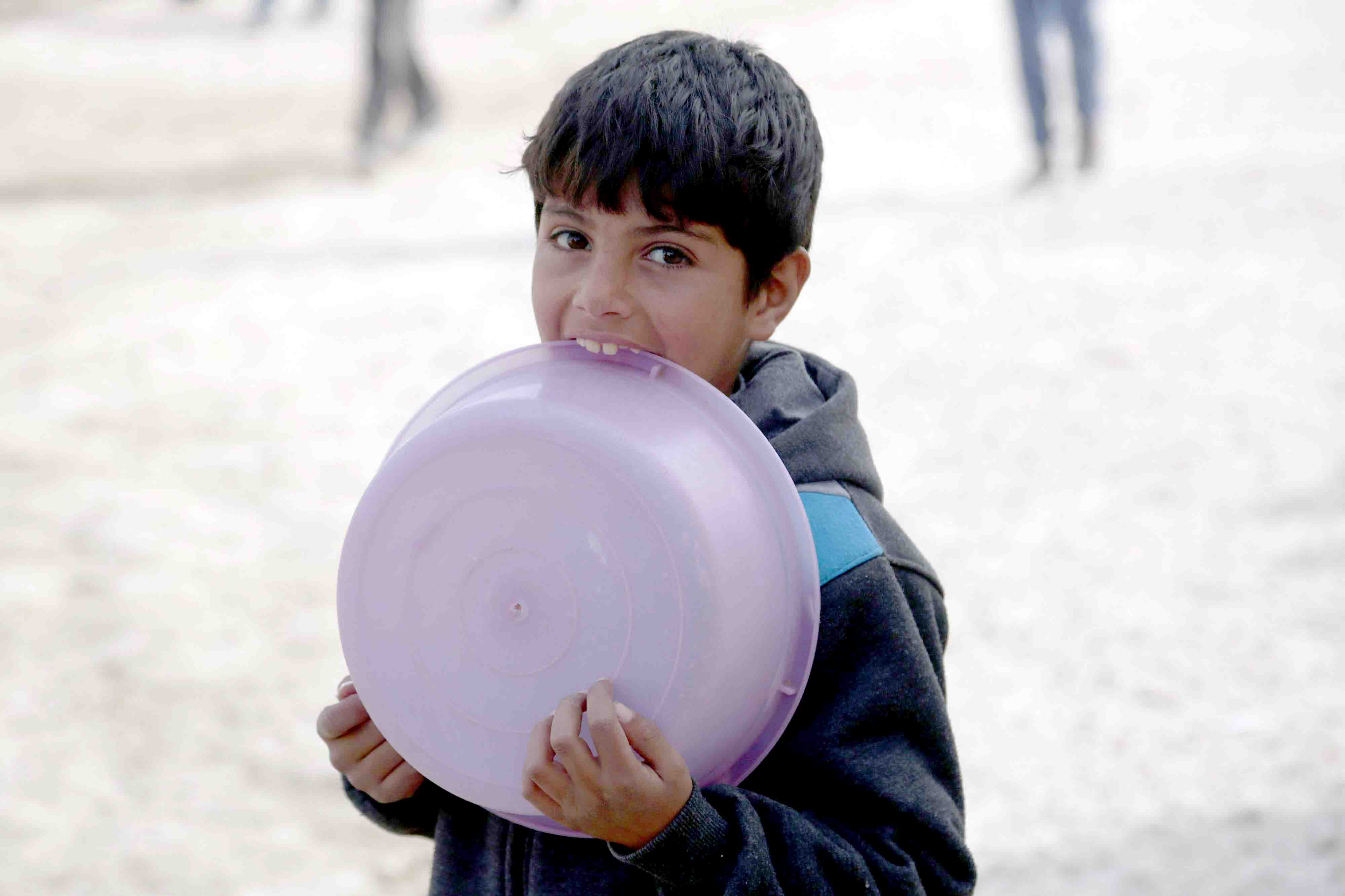 A displaced Syrian boy bites on a plastic bowl at the Ain Issa camp. (AFP)