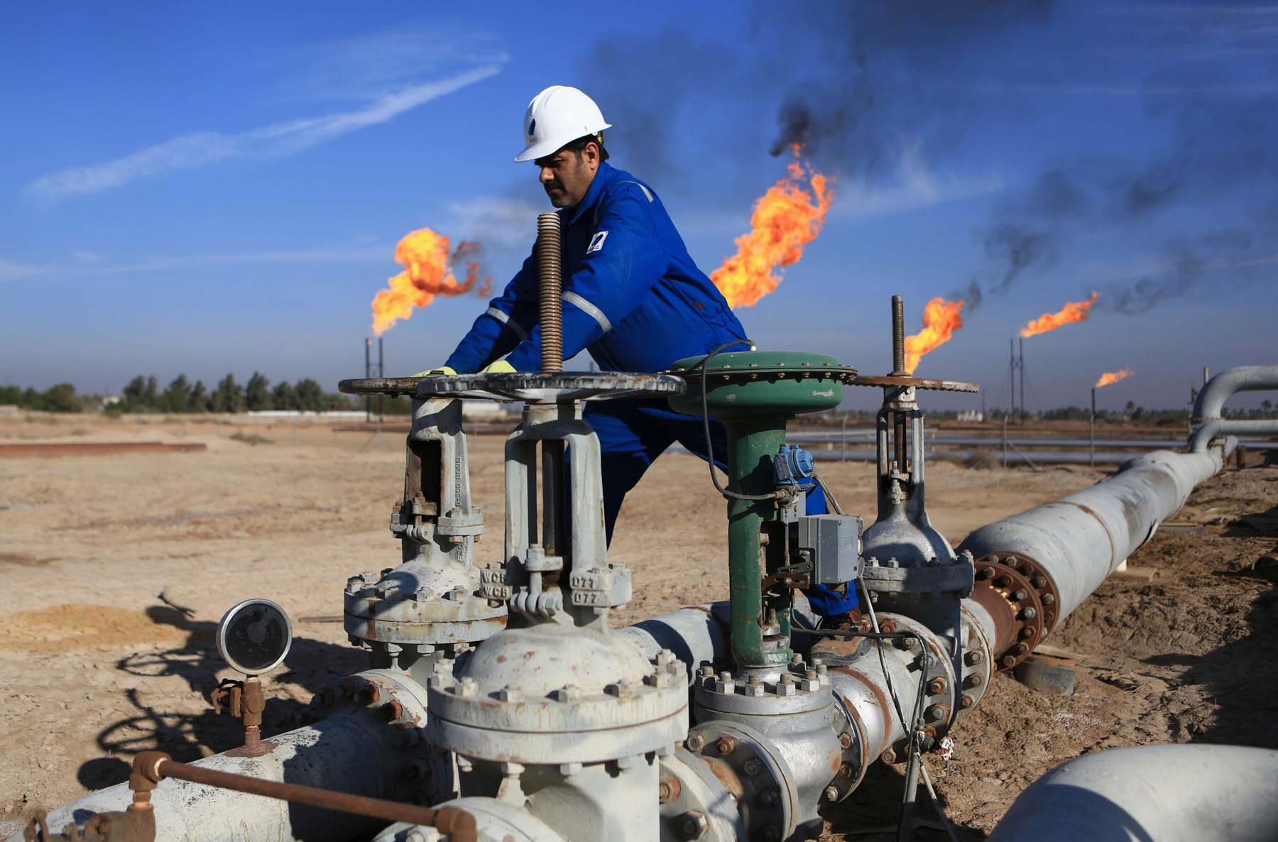 An Iraqi worker operates valves in Nihran Bin Omar oilfield, north of Basra. (AP)