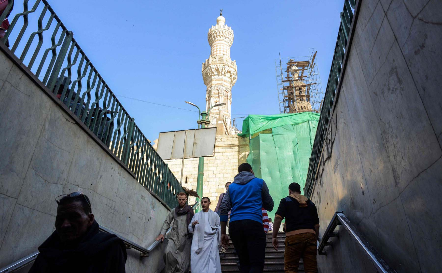 A view of a minaret of al-Azhar mosque in Cairo as passers-by climb out of a pedestrian-crossing tunnel traversing a main street. (AFP)
