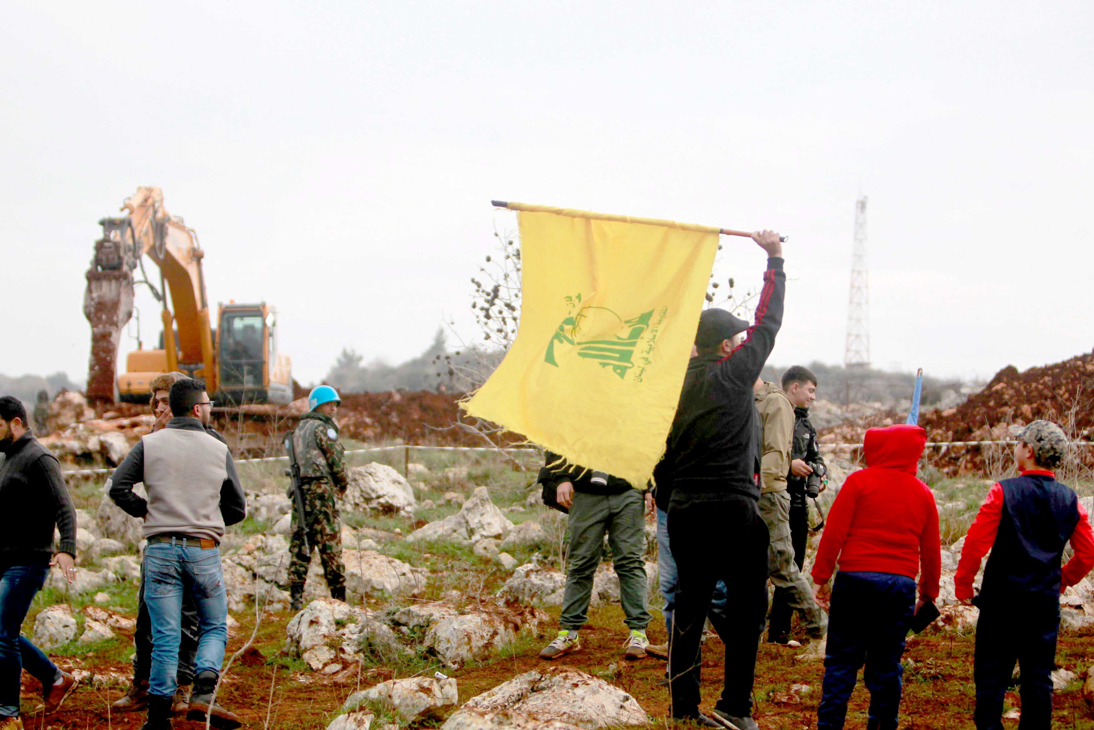New dilemma. A man holds a Hezbollah flag at Meis al-Jabal village in south Lebanon, December 9. (Reuters)