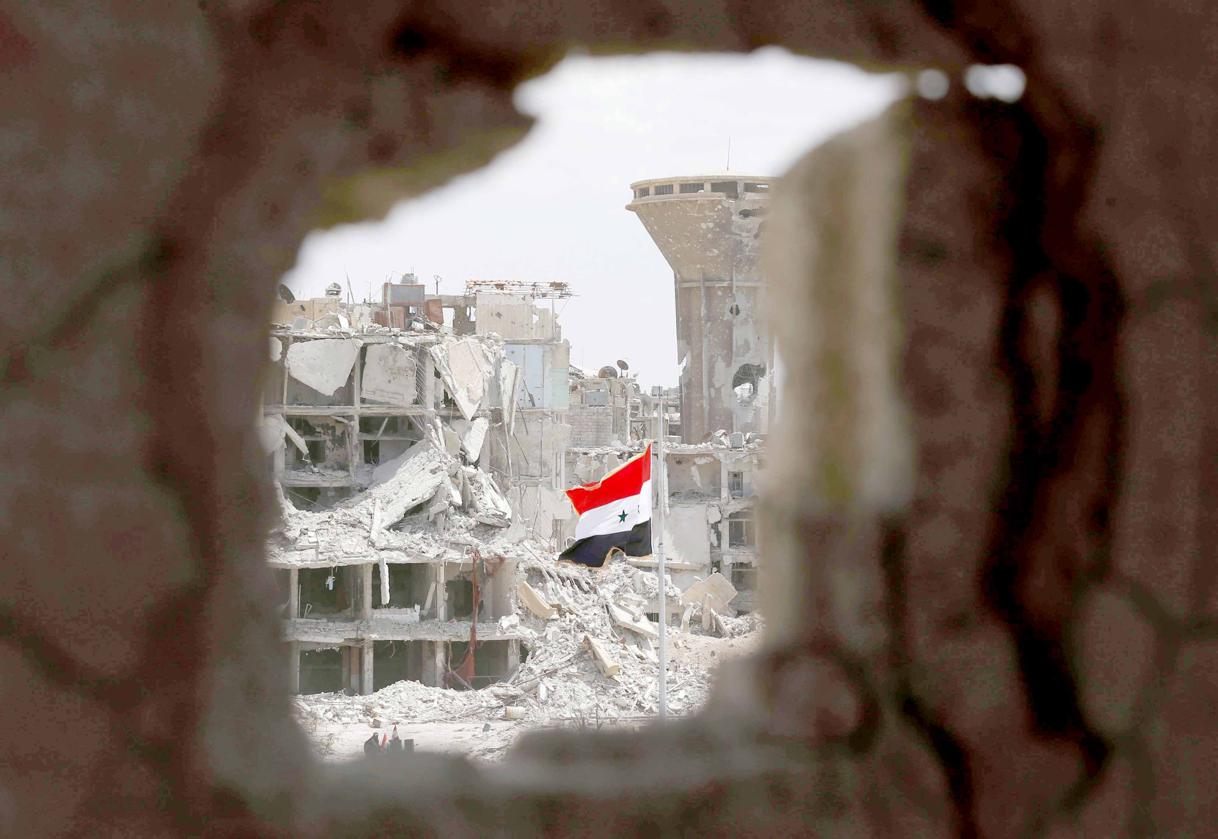 Narrow horizons. A Syrian flag flies in a rubble strewn street at the entrance of the Hajar al-Aswad neighbourhood on the southern outskirts of Damascus. (AFP)