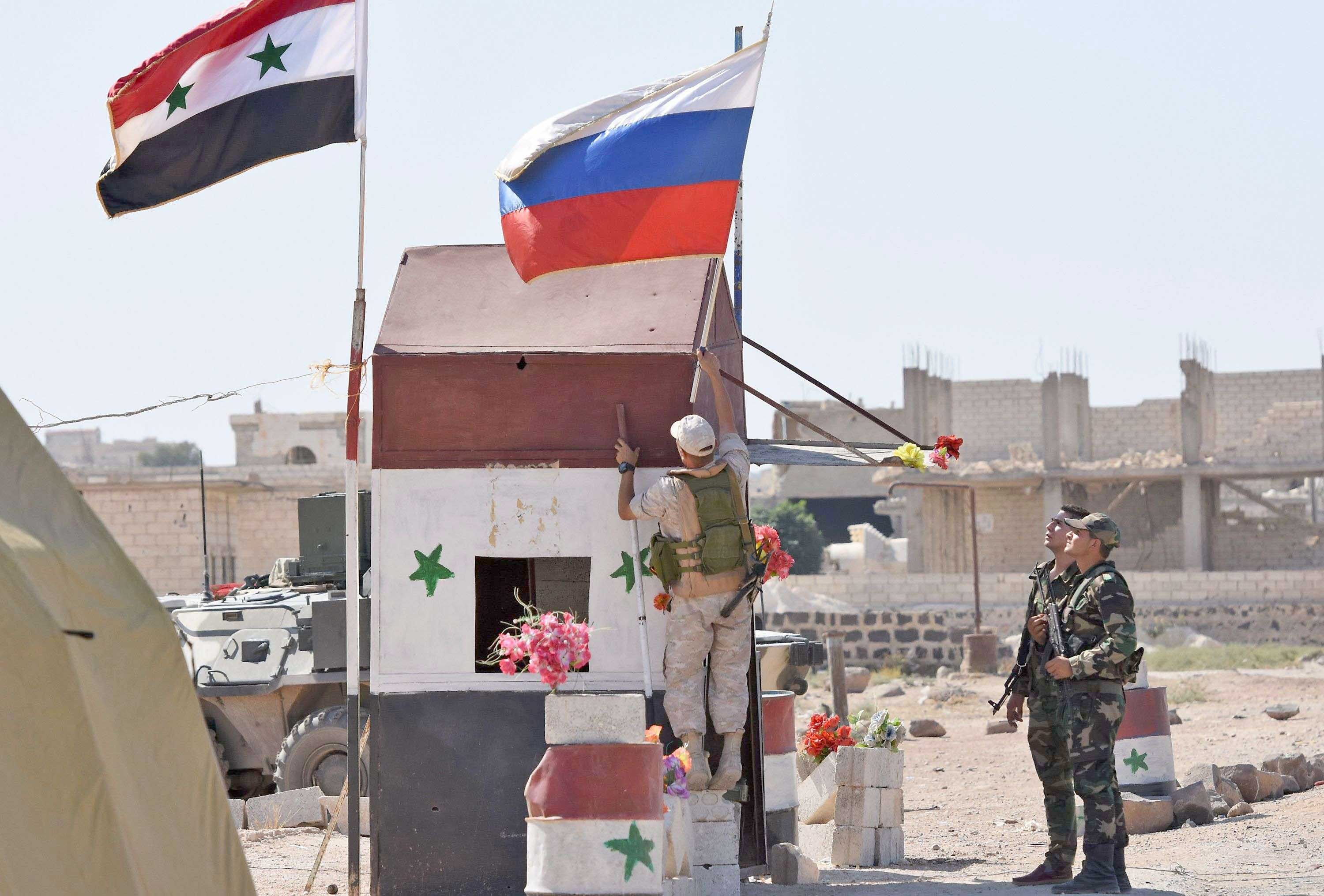 Biggest winner. A Russian soldier (C) places the national flag at the Abu Duhur crossing on the eastern edge of Idlib, September 25. (AFP)