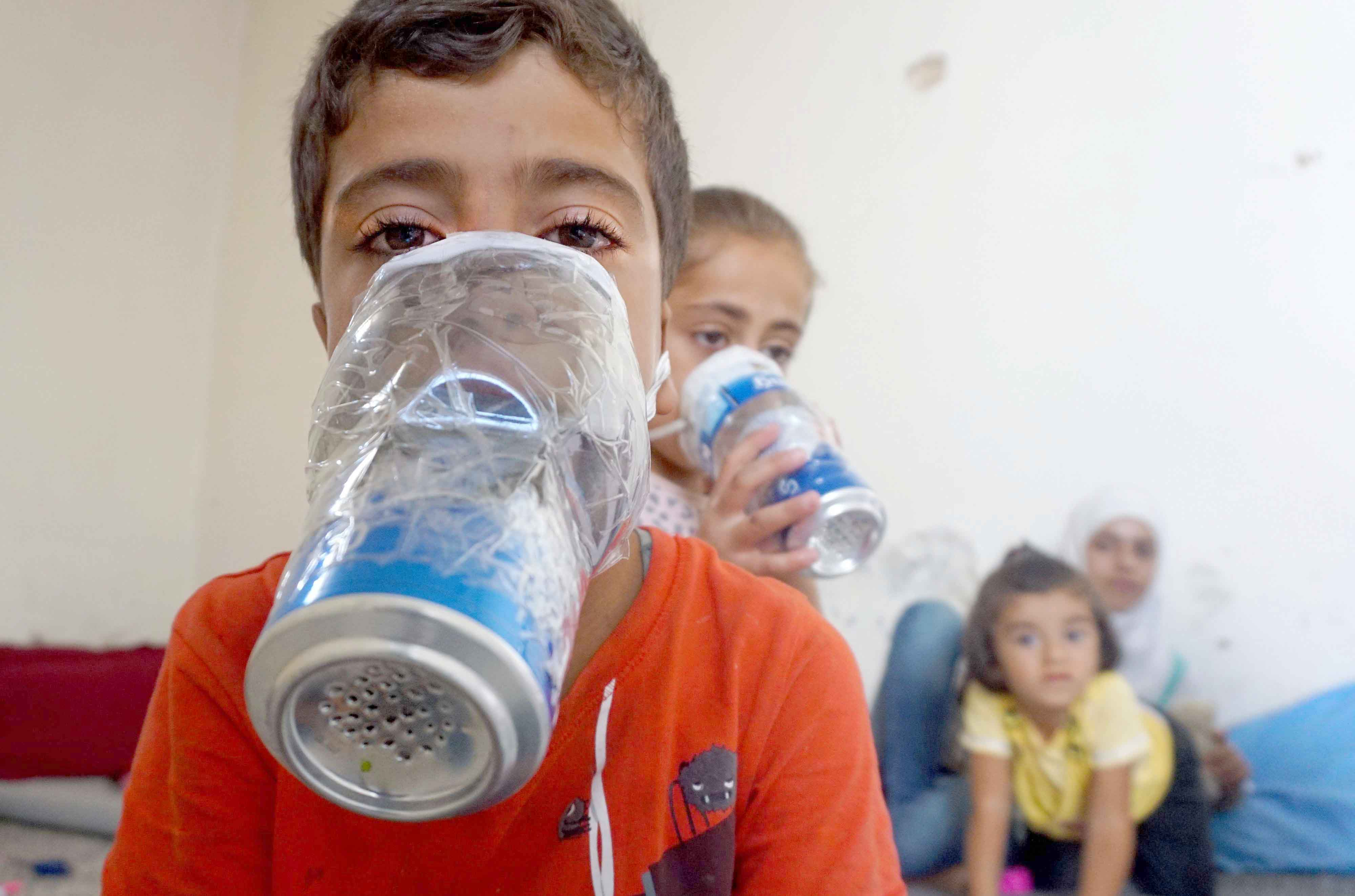 Fear tactics. Children try improvised gas masks in their home in Binnish in Syria's Idlib province, last September.(AFP)