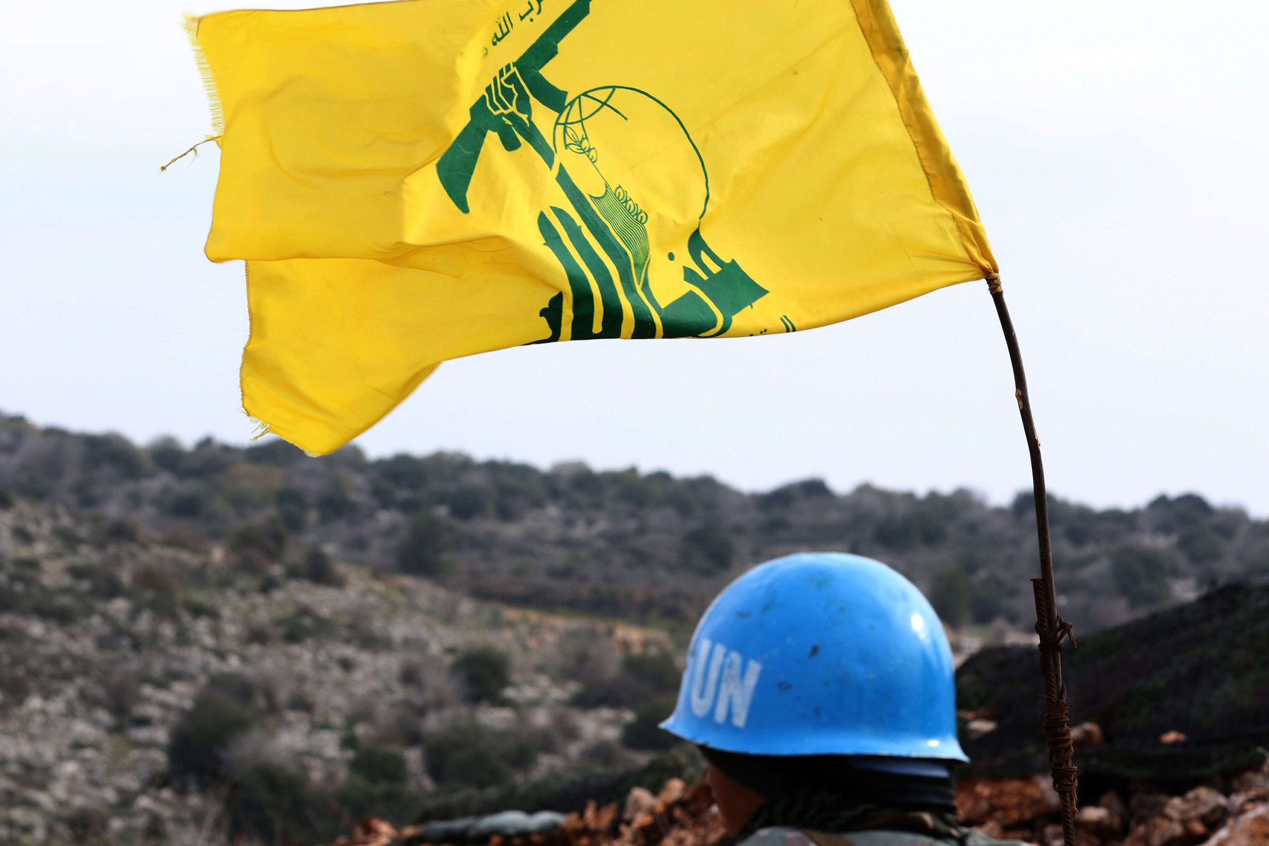 A UN Interim Forces in Lebanon  soldier monitoring the border between Lebanon and Israel. On his right is a flag of the Hezbollah movement. (AFP)