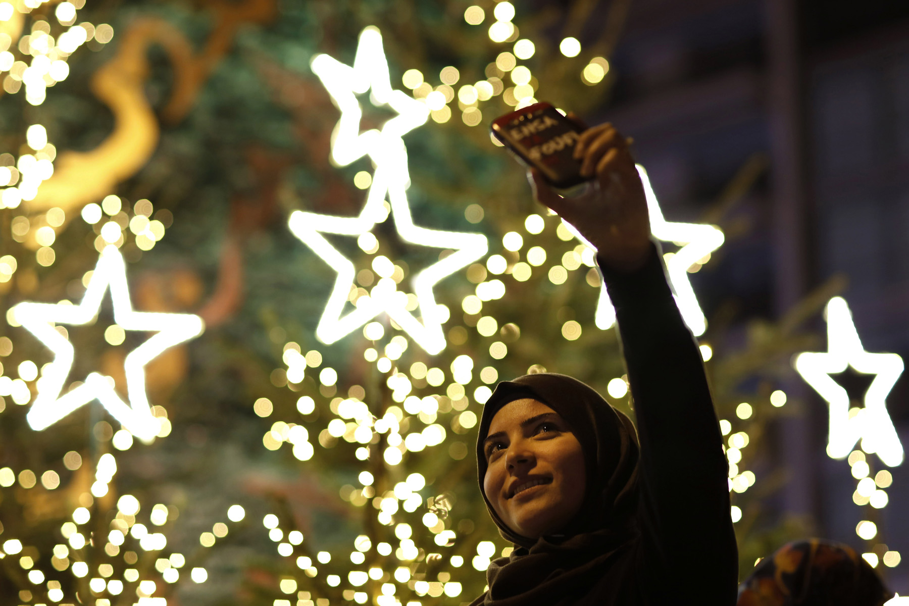 A Muslim woman takes a selfie with Christmas trees in downtown Beirut. (AP)