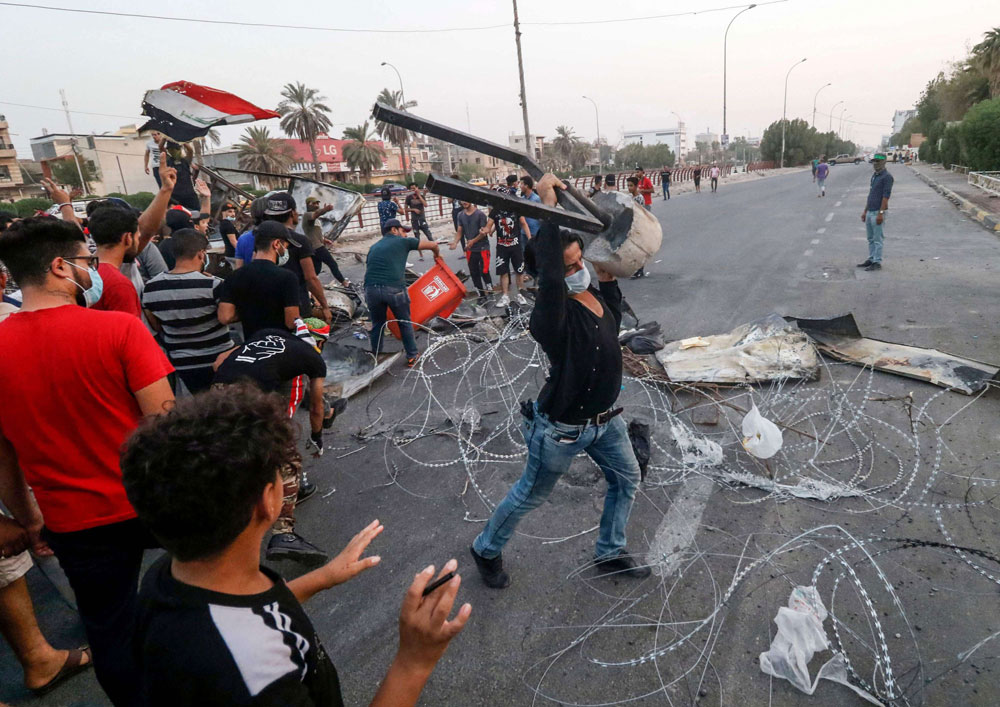 Seething nation. A file picture shows Iraqi protesters clashing with security forces in Basra following a demonstration against corruption, last September. (AFP)
