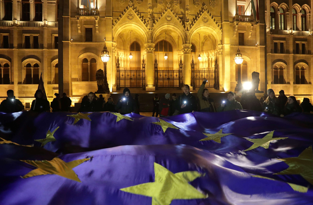 "People hold a big European Union flag during a protest against a proposed new labor law, billed as the ""slave law"", in front of the Parliament building in Budapest, Hungary, on December 18. (Reuters)"
