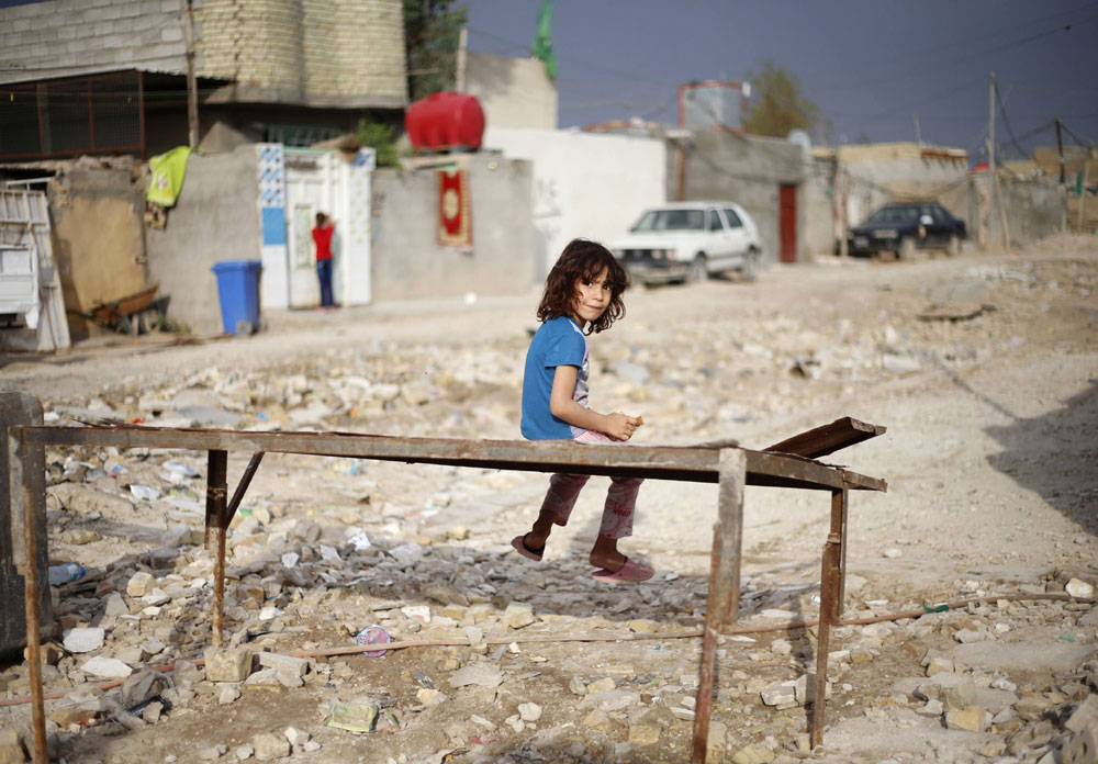 Urban morass. An Iraqi girl sits on a metal bench at her poor neighbourhood in Sadr City in Baghdad. (Reuters)