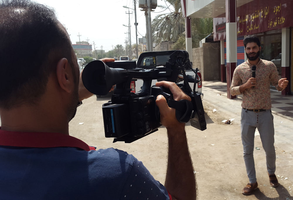 In harm's way. Iraqi journalist Karrar Habeeb (R) while reporting in the southern city of Basra. (Azhar Al-Rubaie)