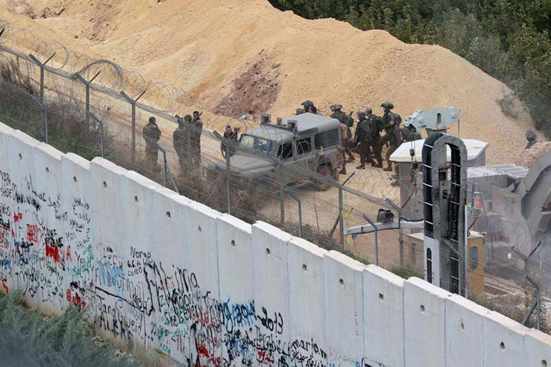 Israeli soldiers gather by an army vehicle across the concrete Lebanon-Israel border wall near the site of an Israeli excavation site, December 5. (AFP)