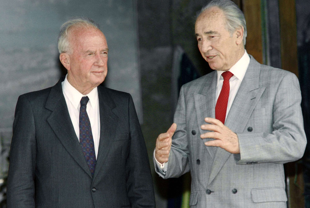 A file photo showing Israeli Prime Minister Yitzhak Rabin (L) listening to Foreign Minister Shimon Peres (R) in Jerusalem,  on May 9, 1993. (AFP)