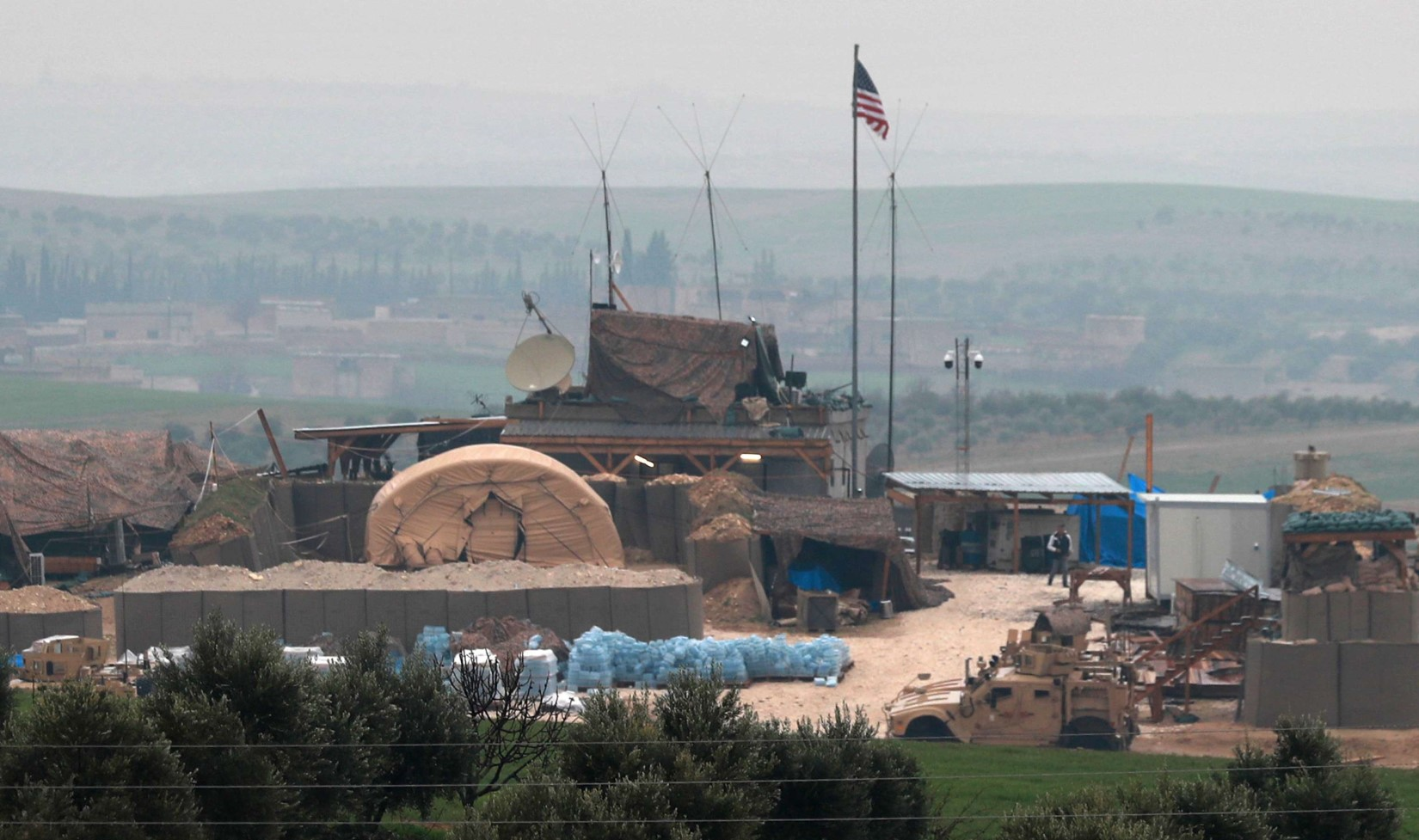 Vehicles and structures of the US-backed coalition forces are seen on the outskirts of the northern Syrian town of Manbij on December 26, 2018. (AFP)