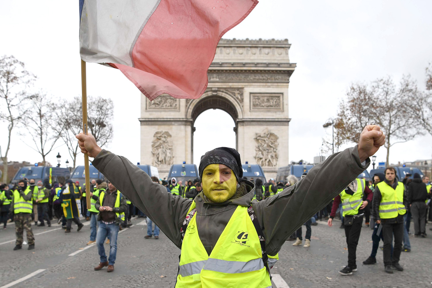 Ripples across the sea. A man wearing a yellow vest holds a French flag on the Champs-Elysees in Paris, December 8. (AFP)