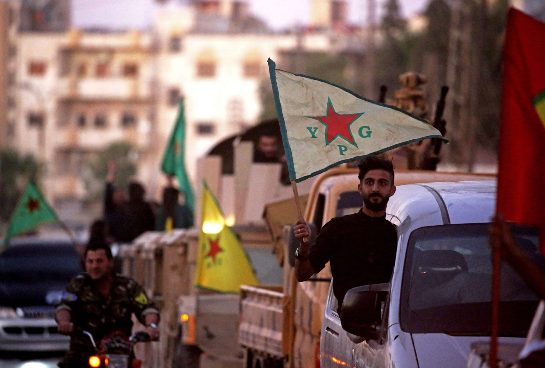Elusive dreams. Supporters and fighters of the Syrian Kurdish People's Protection Units (YPG) drive in the street in Qamishli. (AFP)