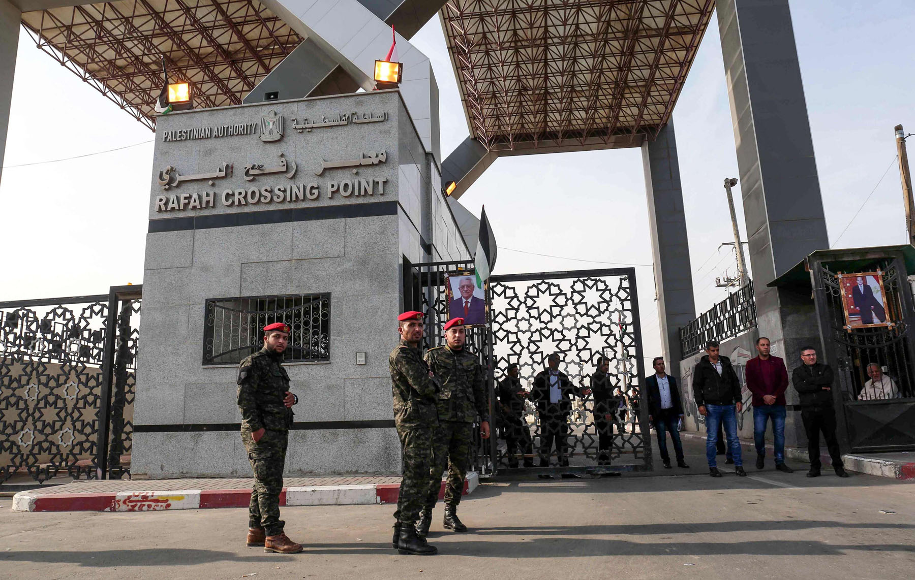 Palestinian security forces loyal to Hamas (L) stand guard near a portrait of Palestinian President Mahmoud Abbas outside the Rafah border crossing with Egypt. (AFP)