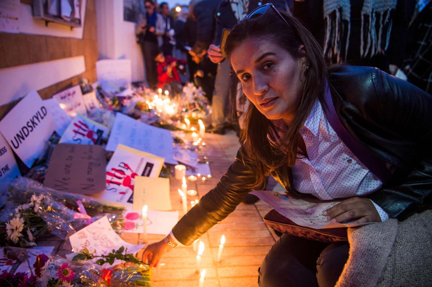 A Moroccan woman places a flower during a vigil for the two Scandinavian hikers outside the Danish Embassy in Rabat, last December. (AFP)