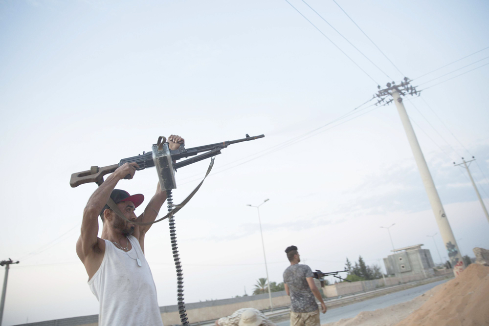 Spraying bullets. Militia fighters shoot at enemy positions during clashes in southern Tripoli. (AP)