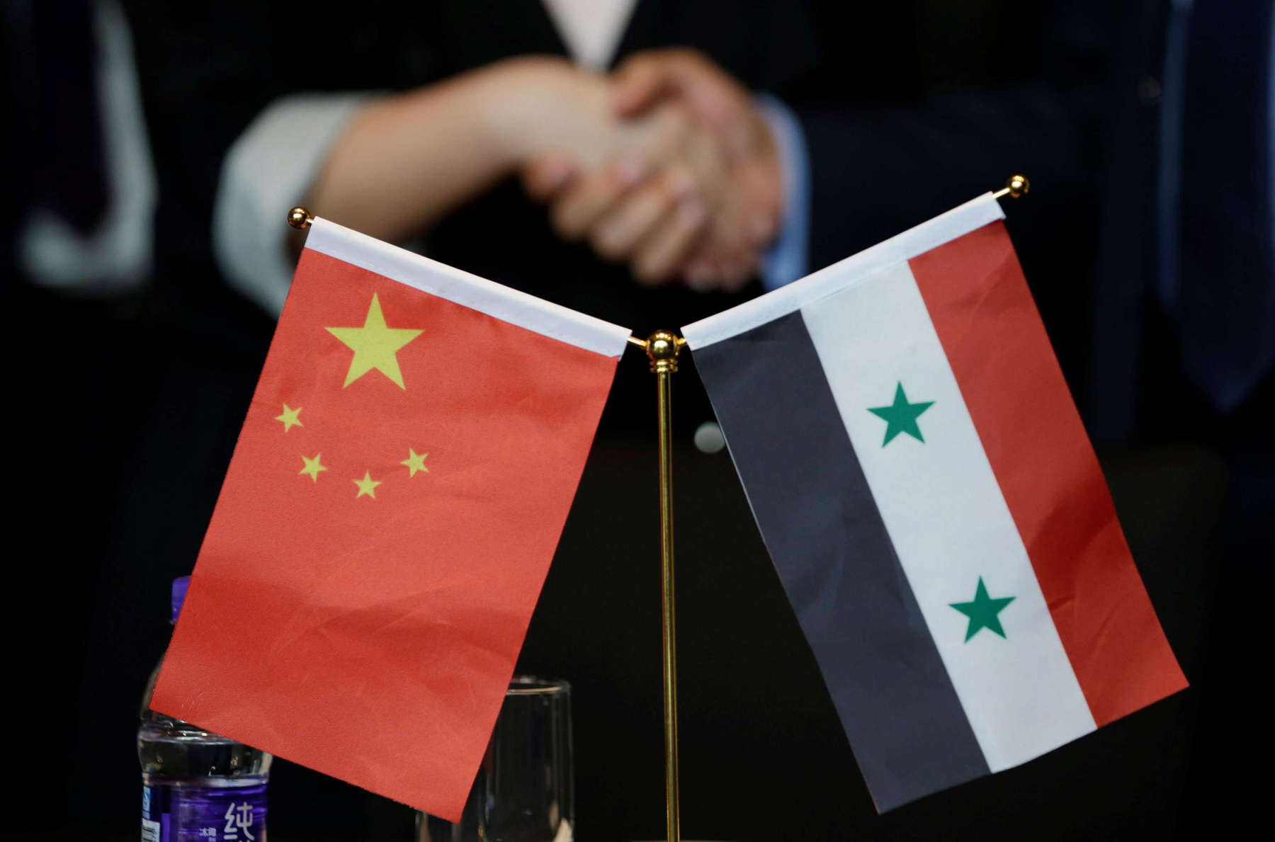 Economic diplomacy. Chinese and Syrian businessmen shake hands behind their national flags during a meeting to discuss Syria's reconstruction in Beijing, last May.  (Reuters)