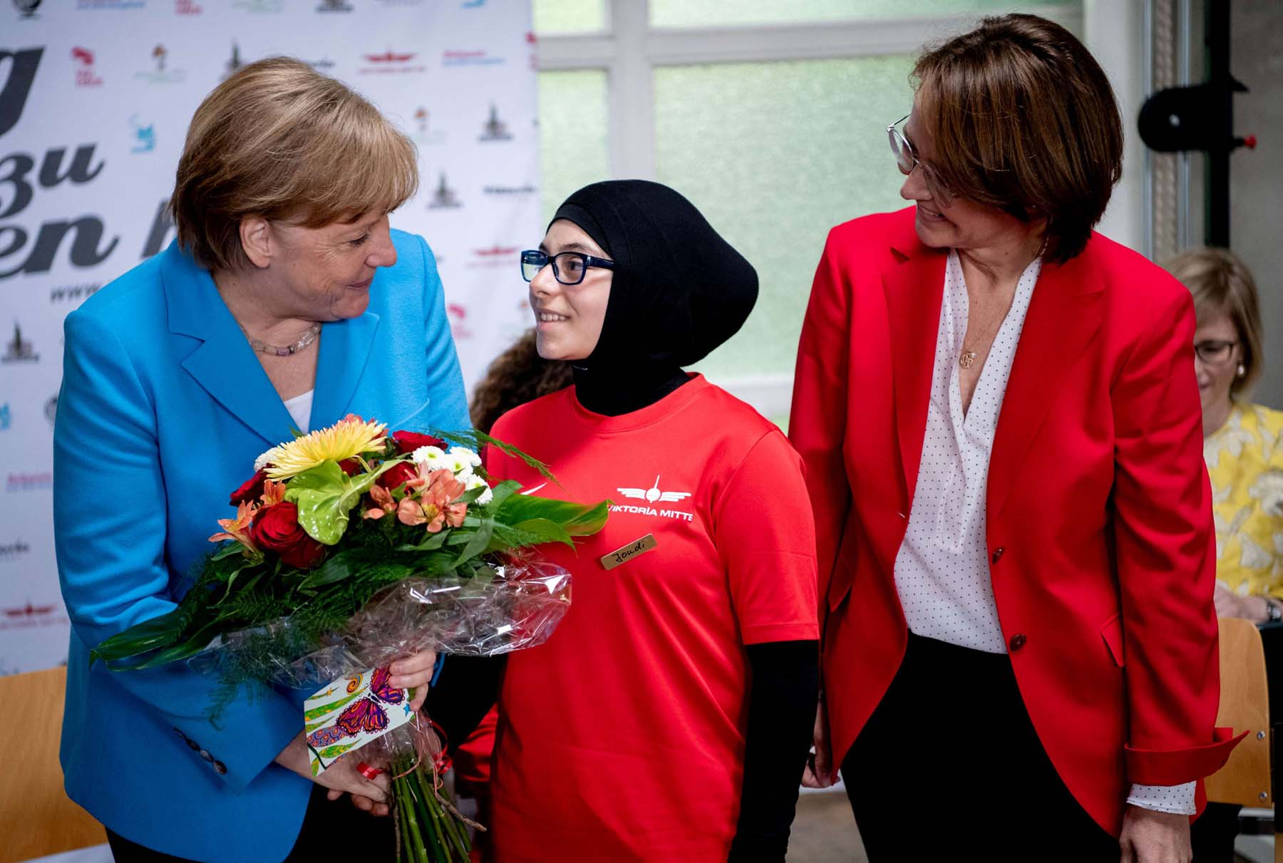 German Chancellor Angela Merkel (L) receives flowers from a Lebanese refugee as Migration Commissioner Annette Widmann-Mauz (R) looks on, last June.                      (Reuters)