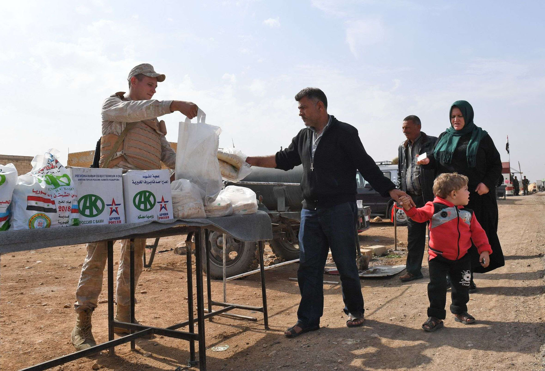 Assertive moves. Syrian families receive aid from Russian soldiers at the Abu Duhur crossing on the eastern edge of Idlib province, last October. (AFP)
