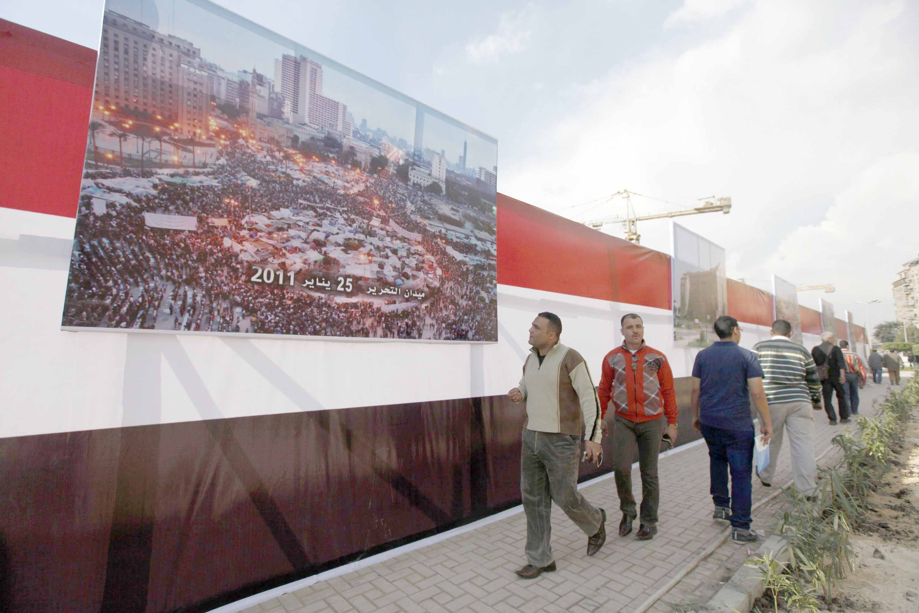People walk in front of pictures of Tahrir Square to commemorate those killed during the Mohamed Mahmoud Street battles in 2011. (Reuters)